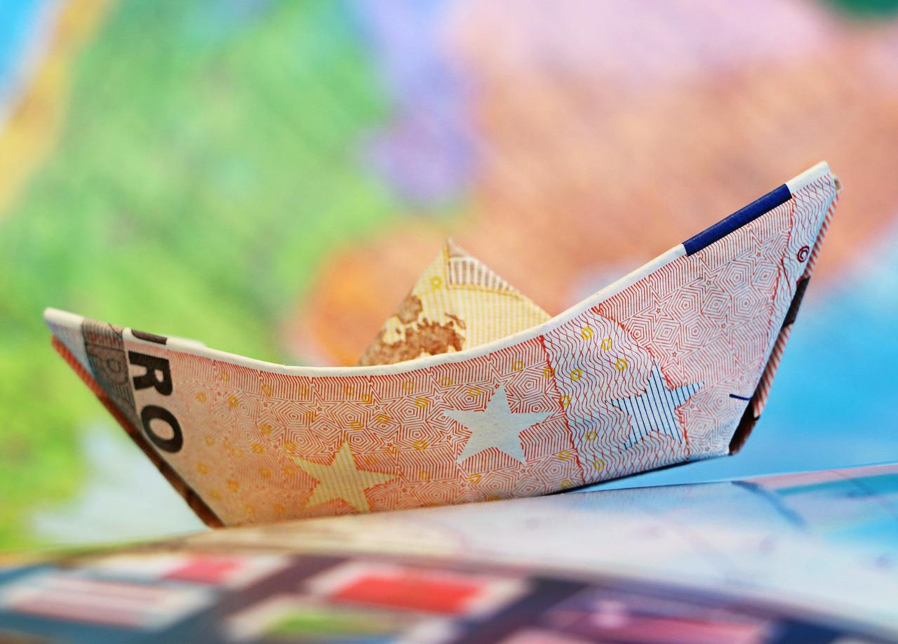 Een kleurrijke afbeelding met de kleuren groen, paars, blauw en oranje als hoofdkleur. In het midden zie je bootje gevouwen van een briefje van 50 euro.