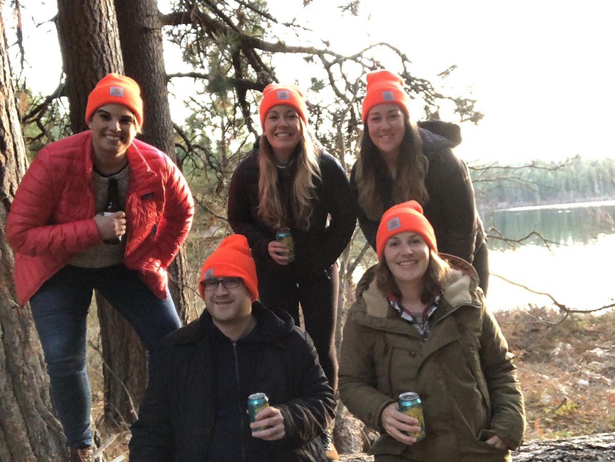 Group of people outside wearing orange hats.