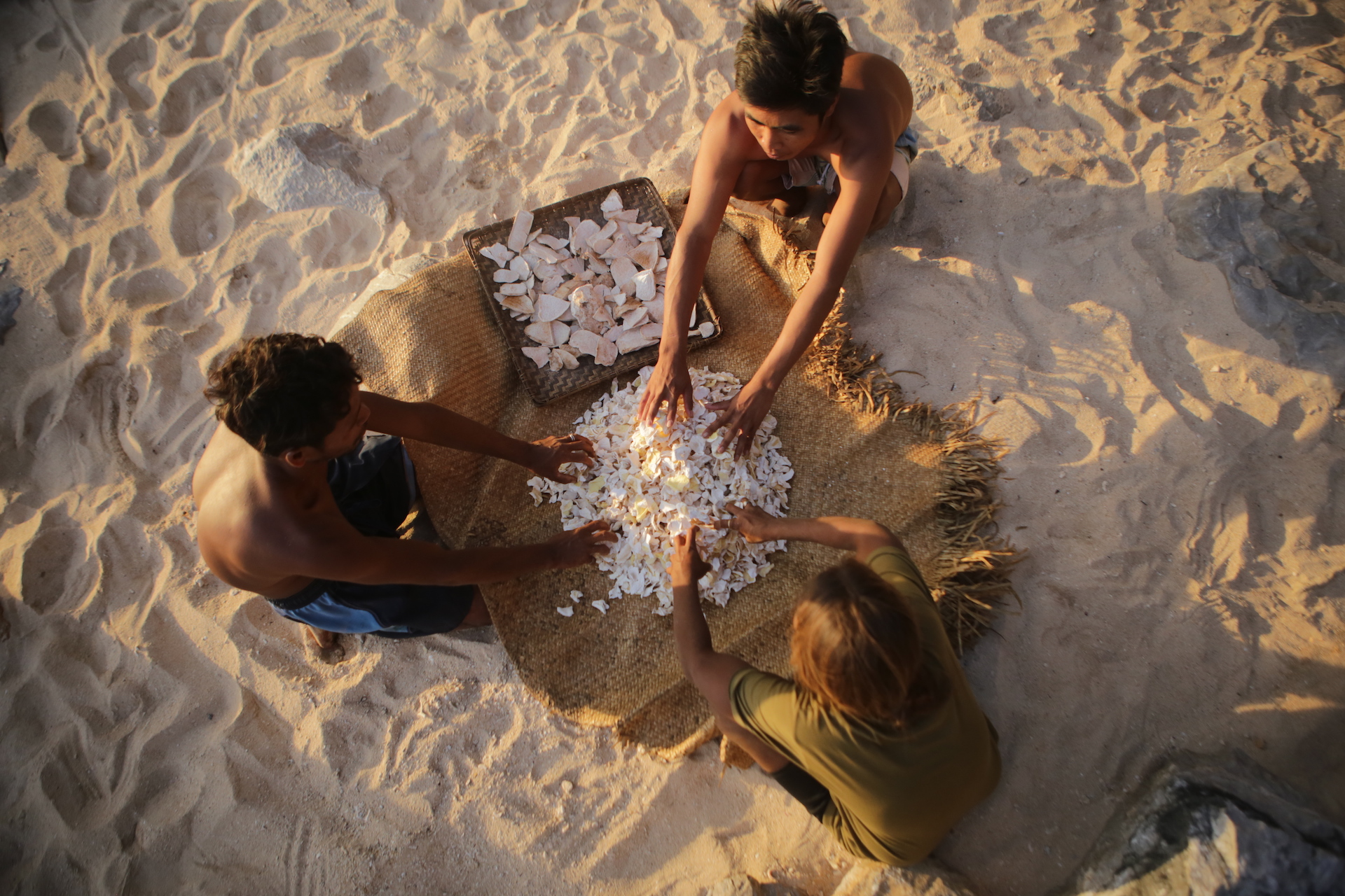 Tagbanua sorting out shells on the beach