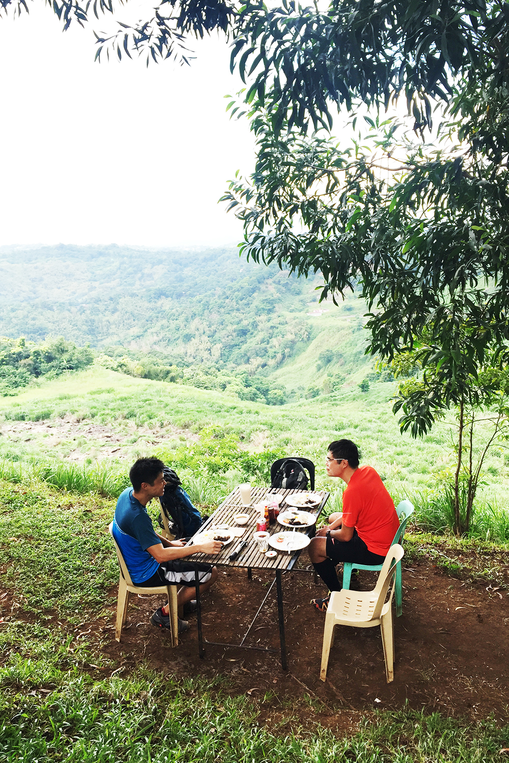 Two bikers eating breakfast overlooking mountains in Tanay Rizal