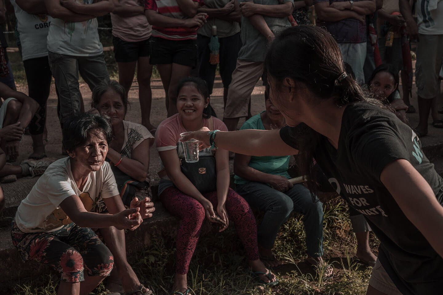 Jenica Dizon offers a plastic cup of filtered water to the community at Diapila.