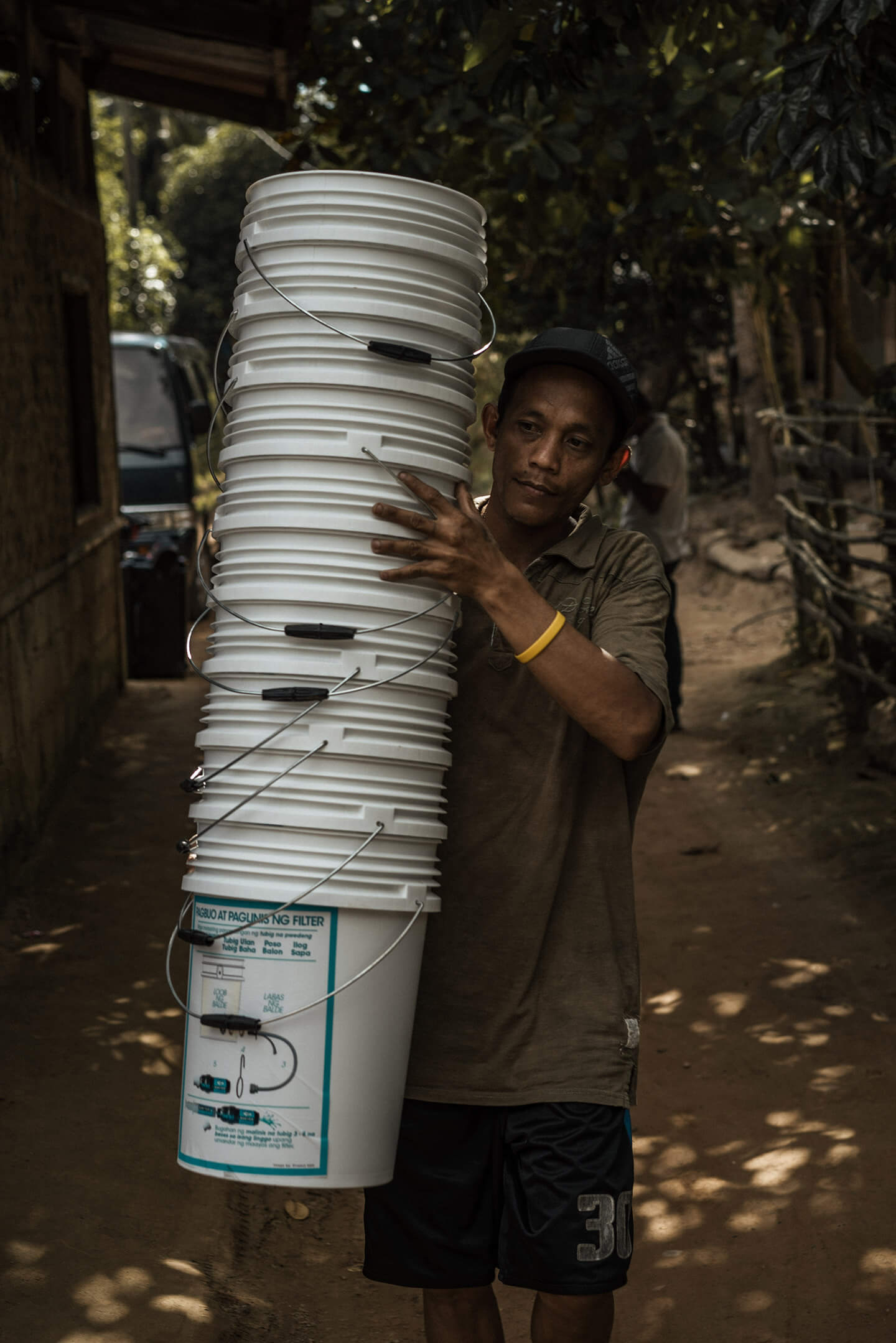 A Palawan local carrying white pails for getting filtered water.