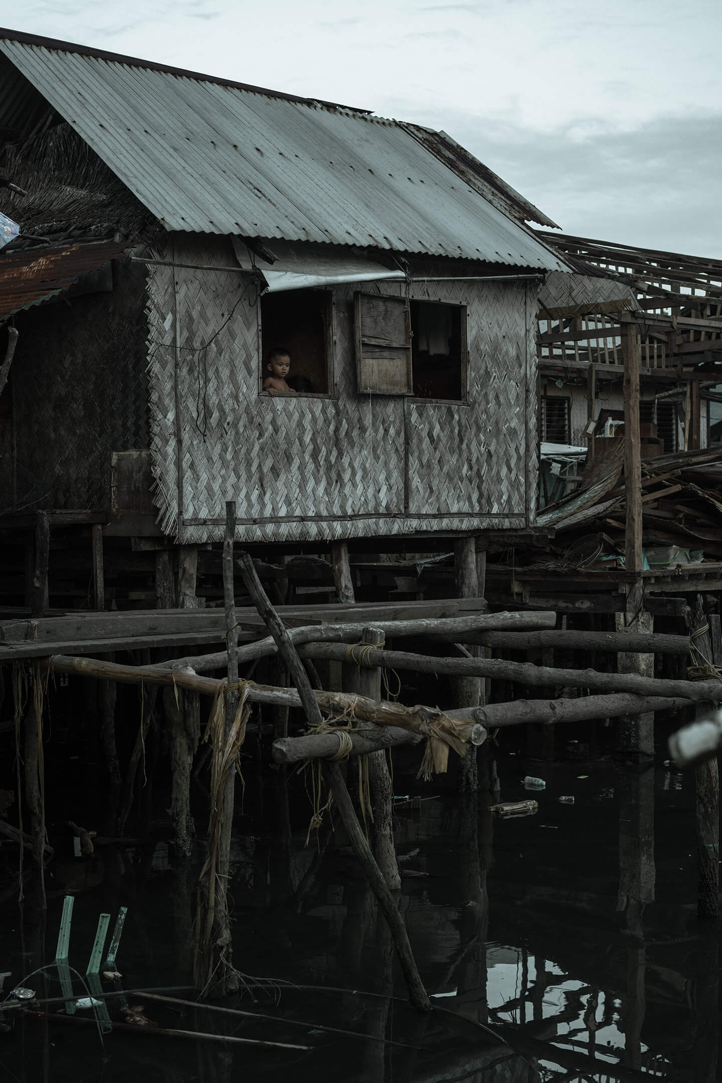 A small child looks over the window of their house on stilts above the water.