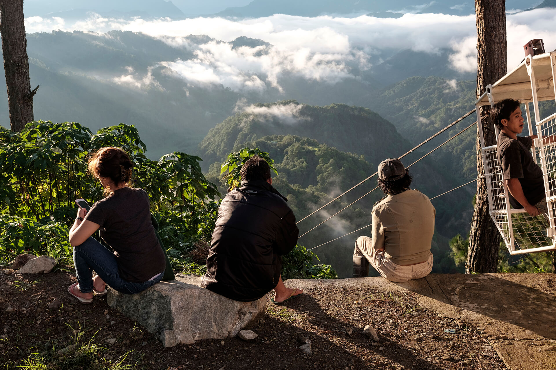 Locals and traveller alike sit on the ledge overlooking the mountain tops of Benguet and an aged container contraption