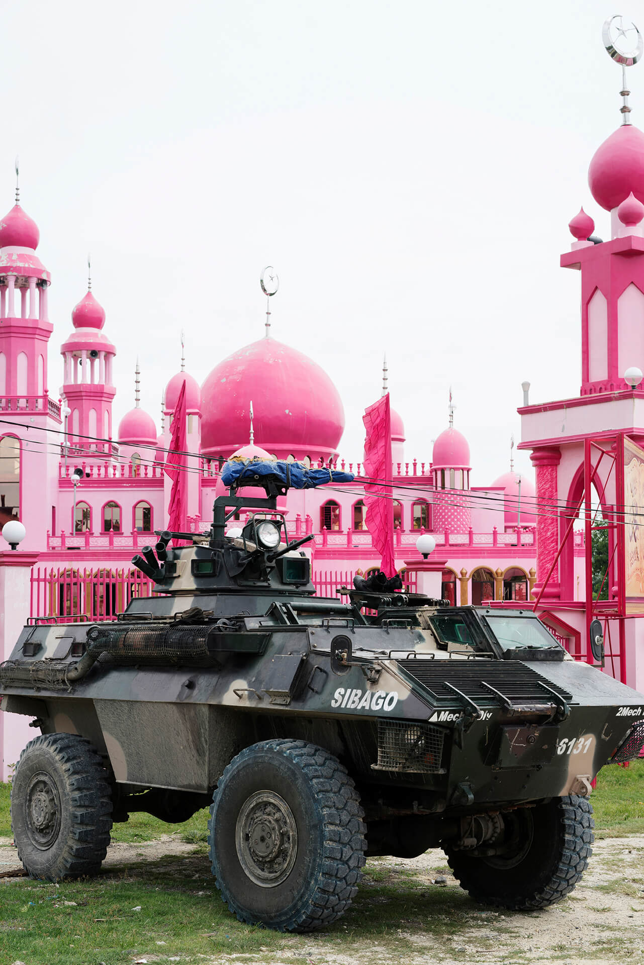 A military tanker is stationed in front of the famous pink masjid.
