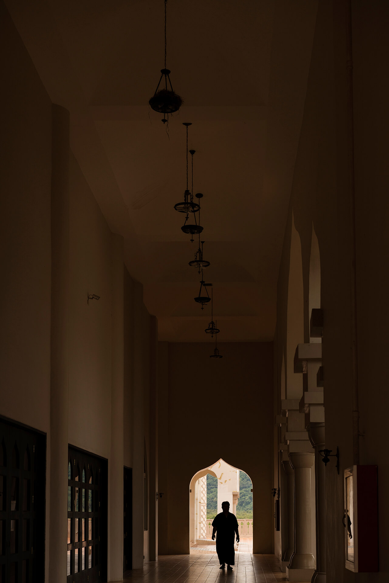 A Muslim man walking along the peaceful halls of a mosque