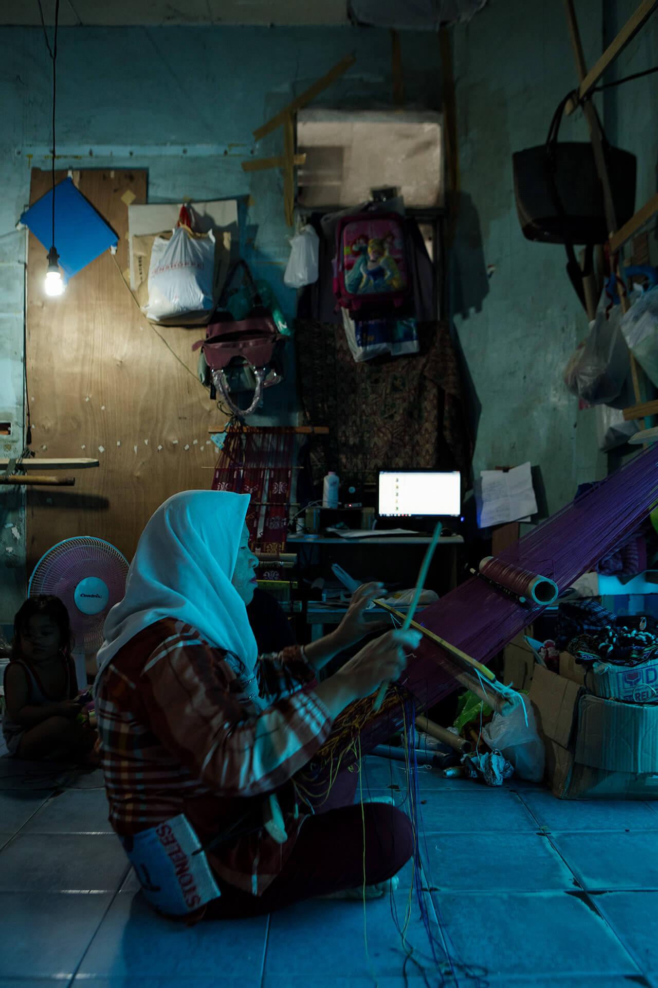 Maranao bakwit (refugee) weaving on the floor using a scavenged makeshift loom.