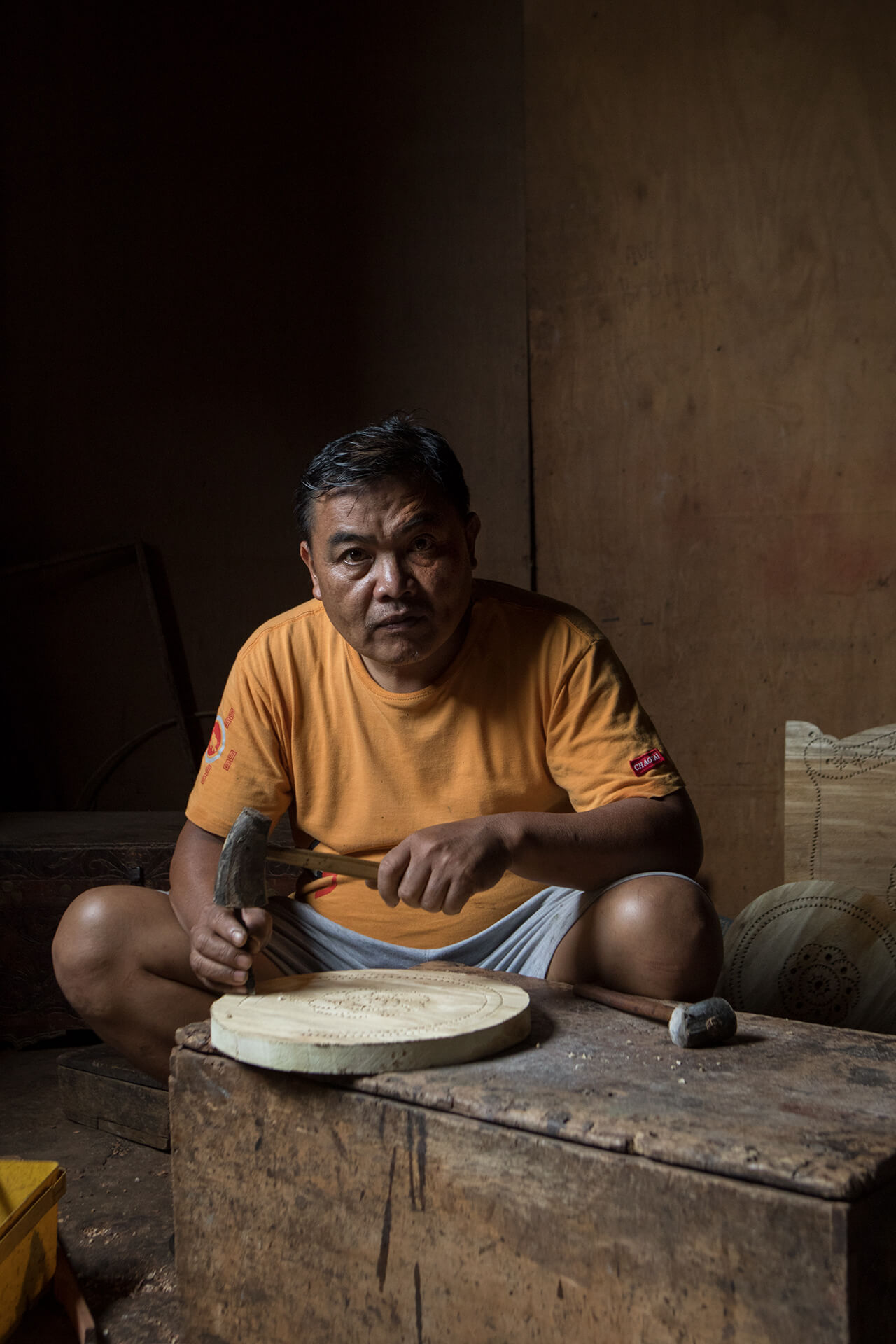 Maranao artisinal craftsman working-up okir patterns on a wooden plate.