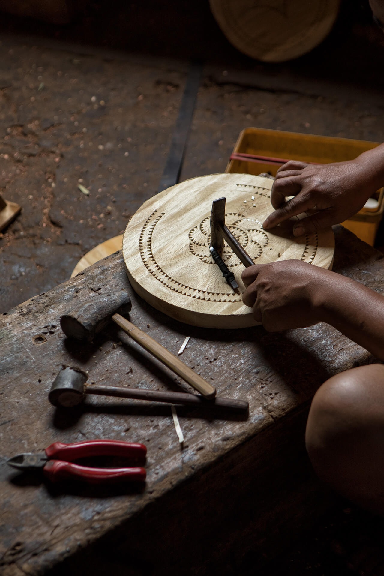 Maranao artisinal craftsman hammering geometric and floral patterns on a wooden plate.