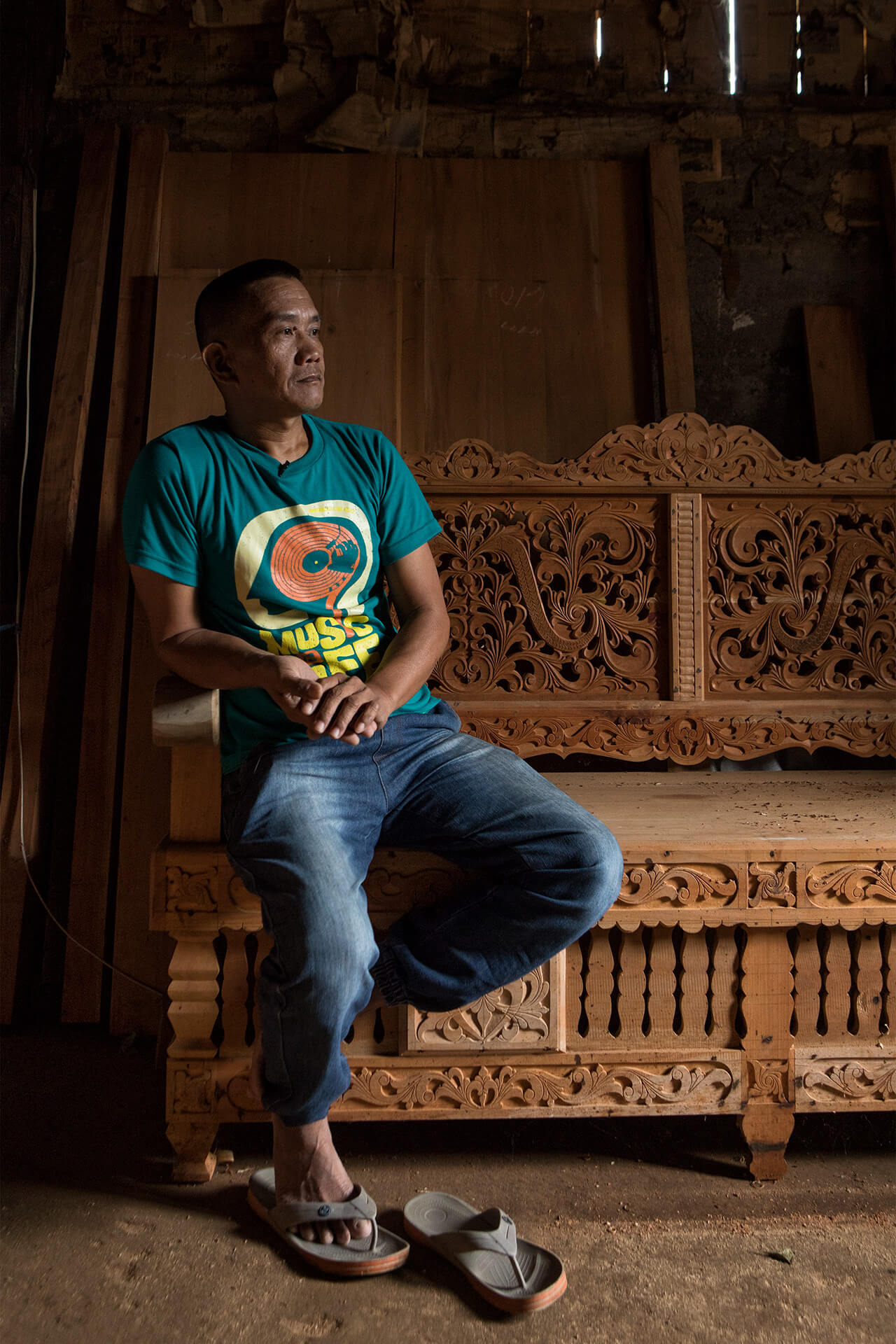 Maranoan craftsman sitting on his finished bench with intricate floral carvings