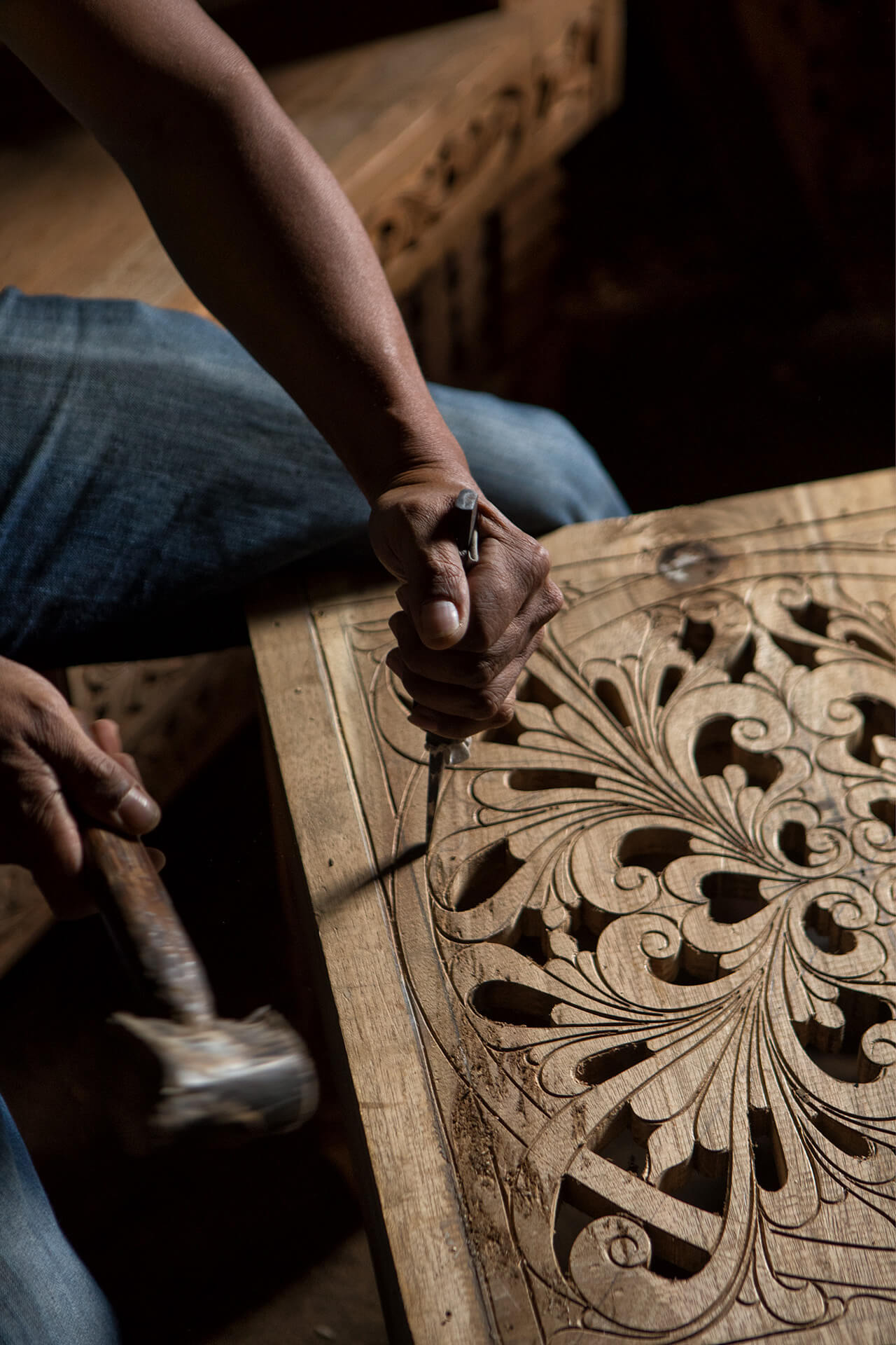 A worksman in action: intricate wood carvings on a piece of furniture