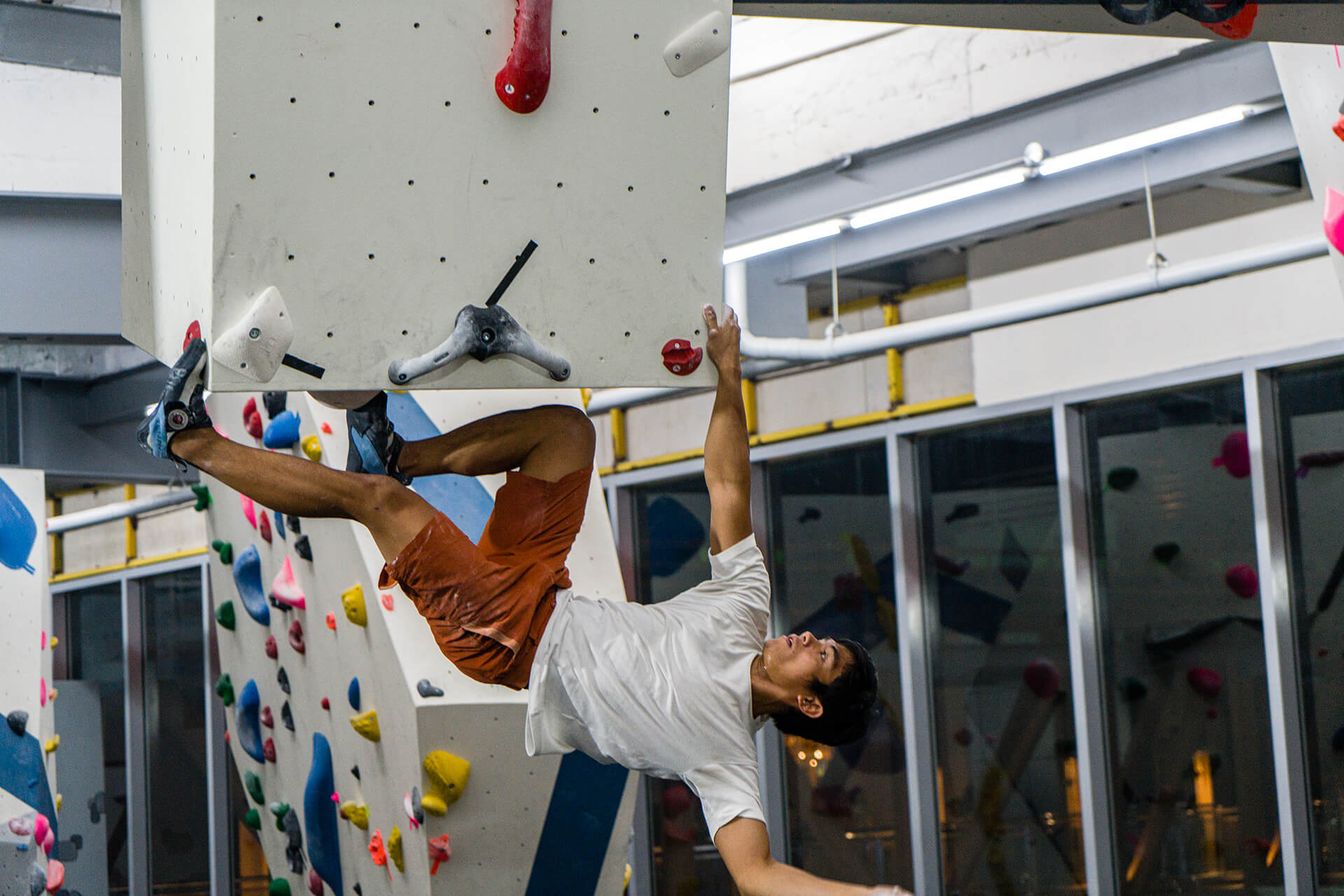 Bouldering athlete hanging by a single grip from the ledge
