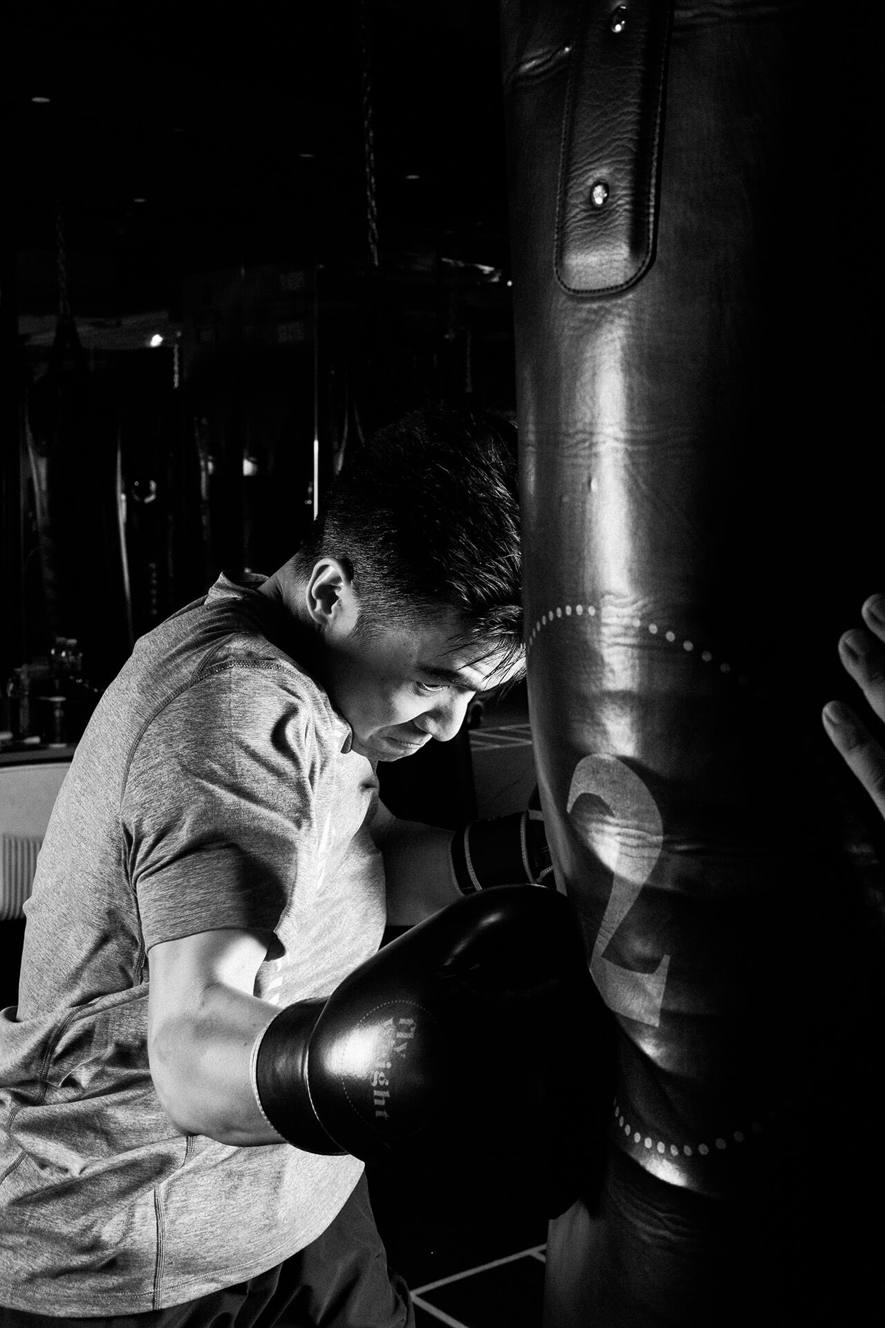 A black & white portrait of a male boxer practicing his jabs.