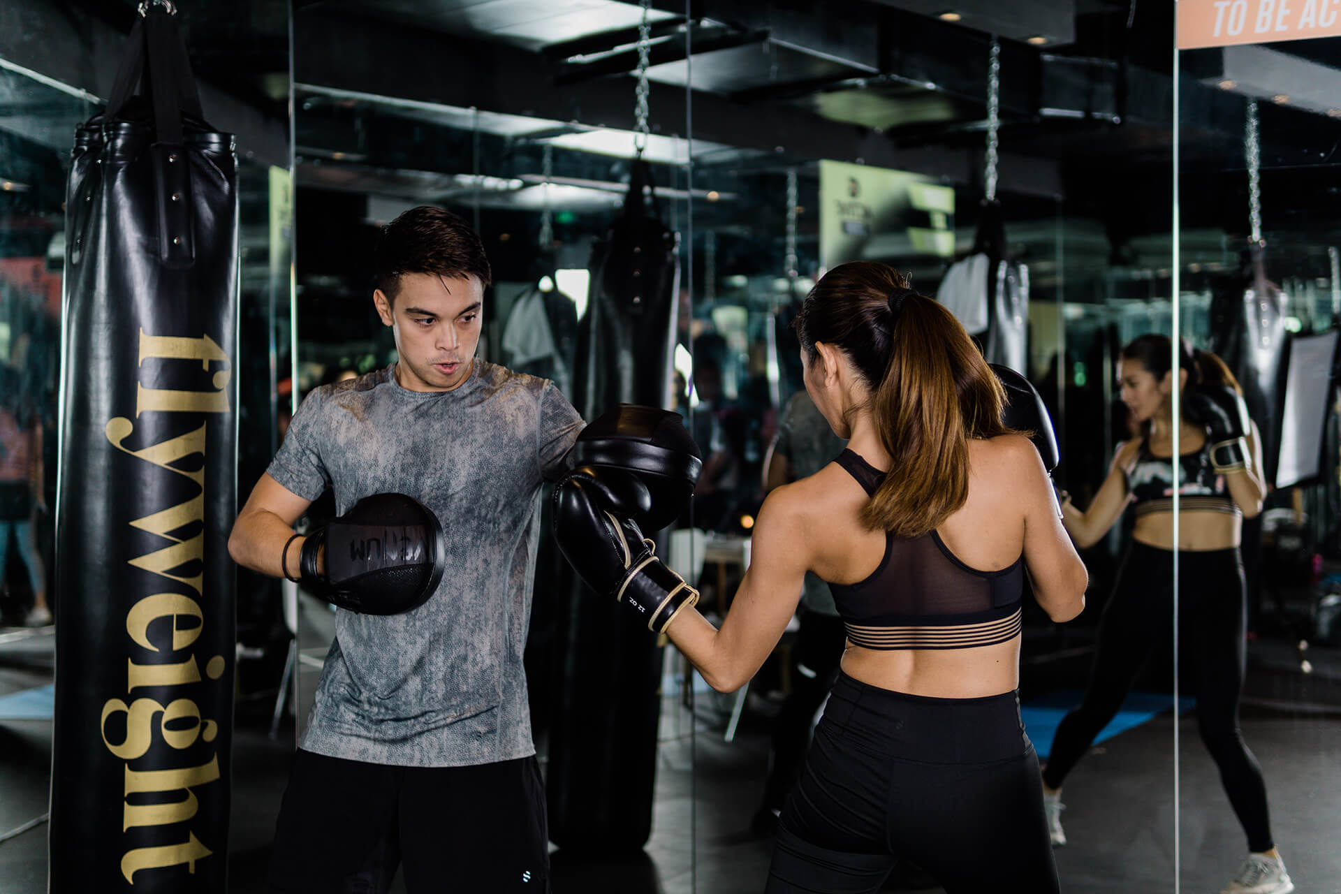 A sharp action shot of a male and female boxer sparring in front of glass mirrors.