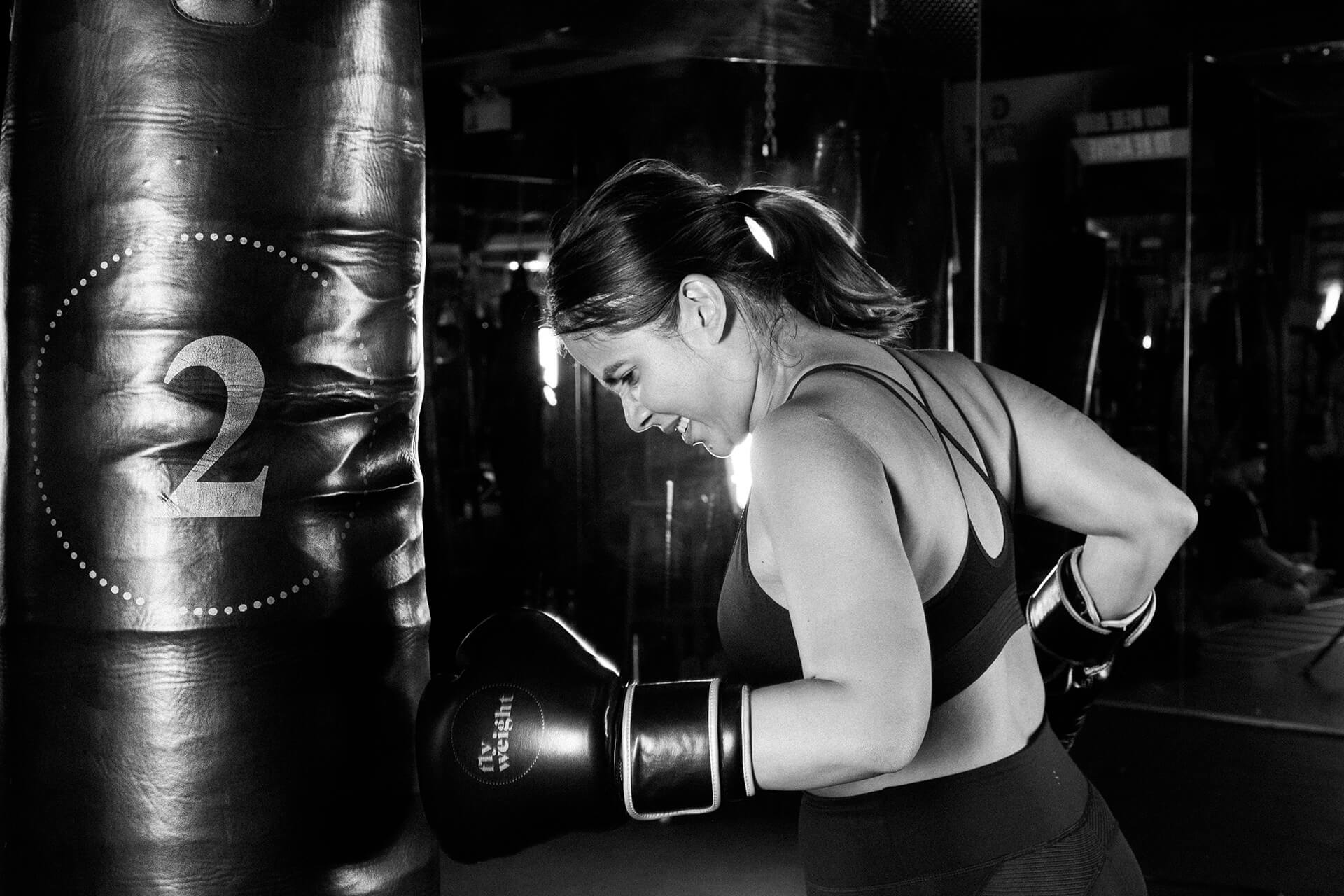 A dramatic and crystal clear action shot of a female boxer practicing her jabs.