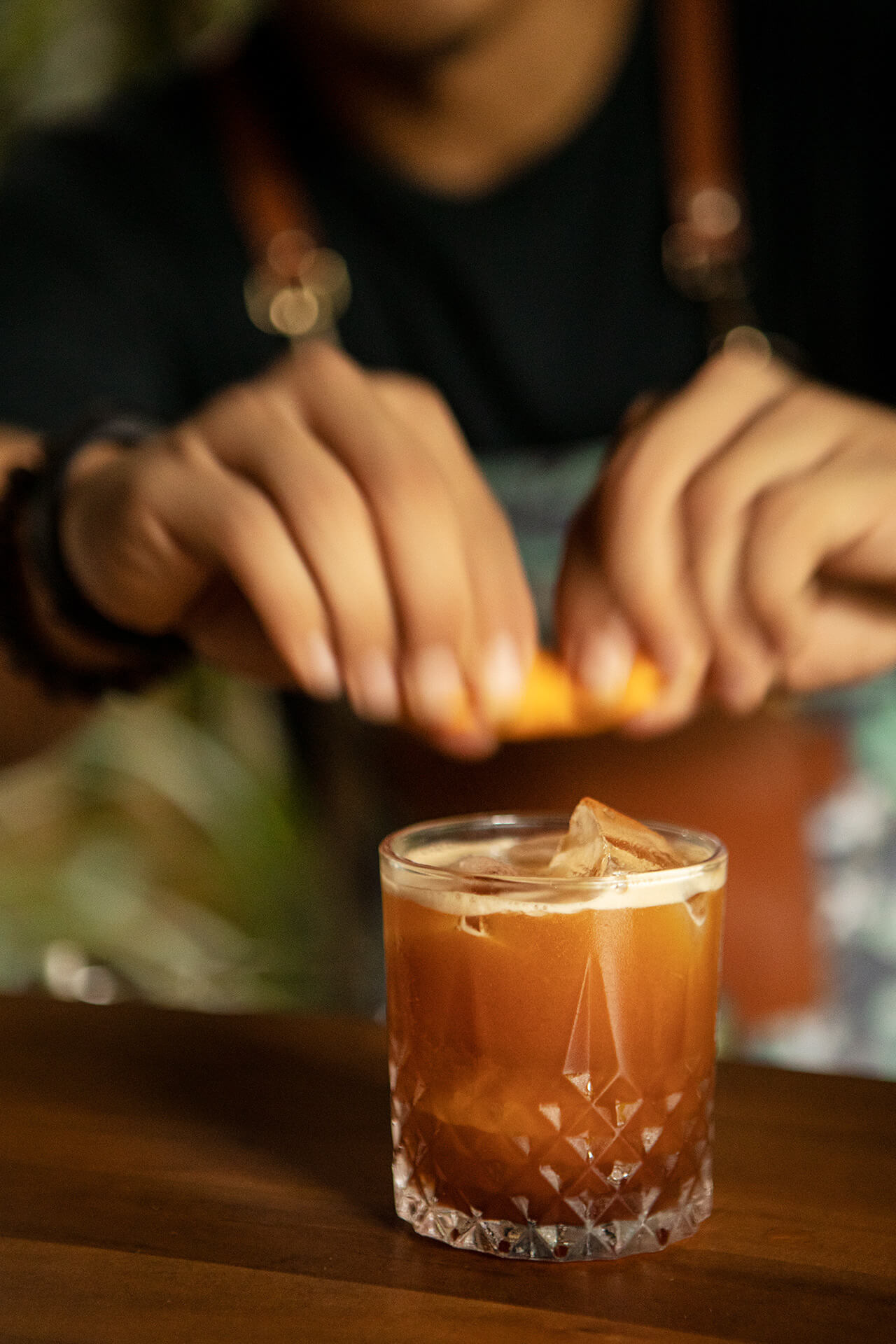 Ken Alonso garnishing a tapuey cocktail with a slice of orange.