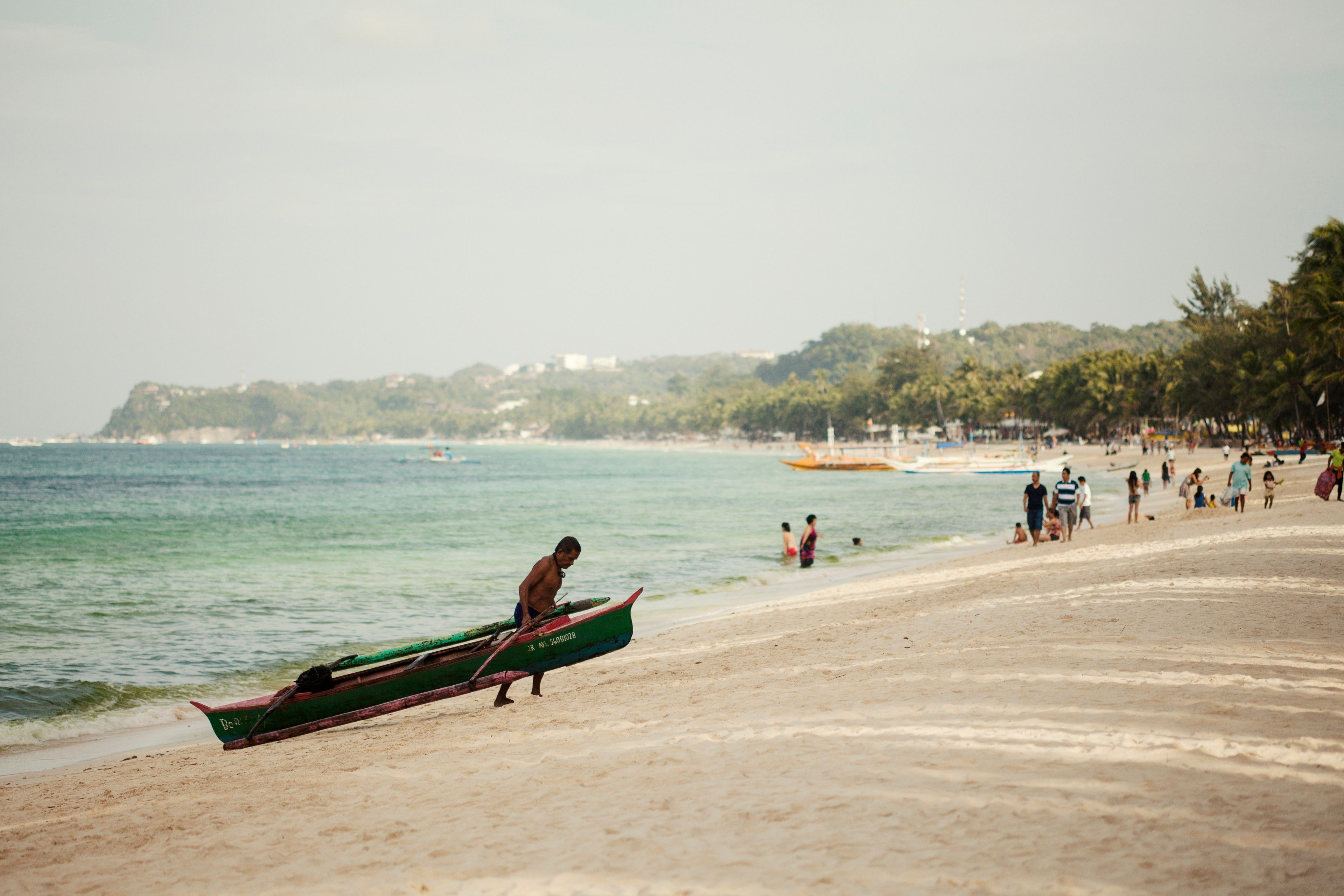 Photo of a Boracay local dragging his boat to the shore.