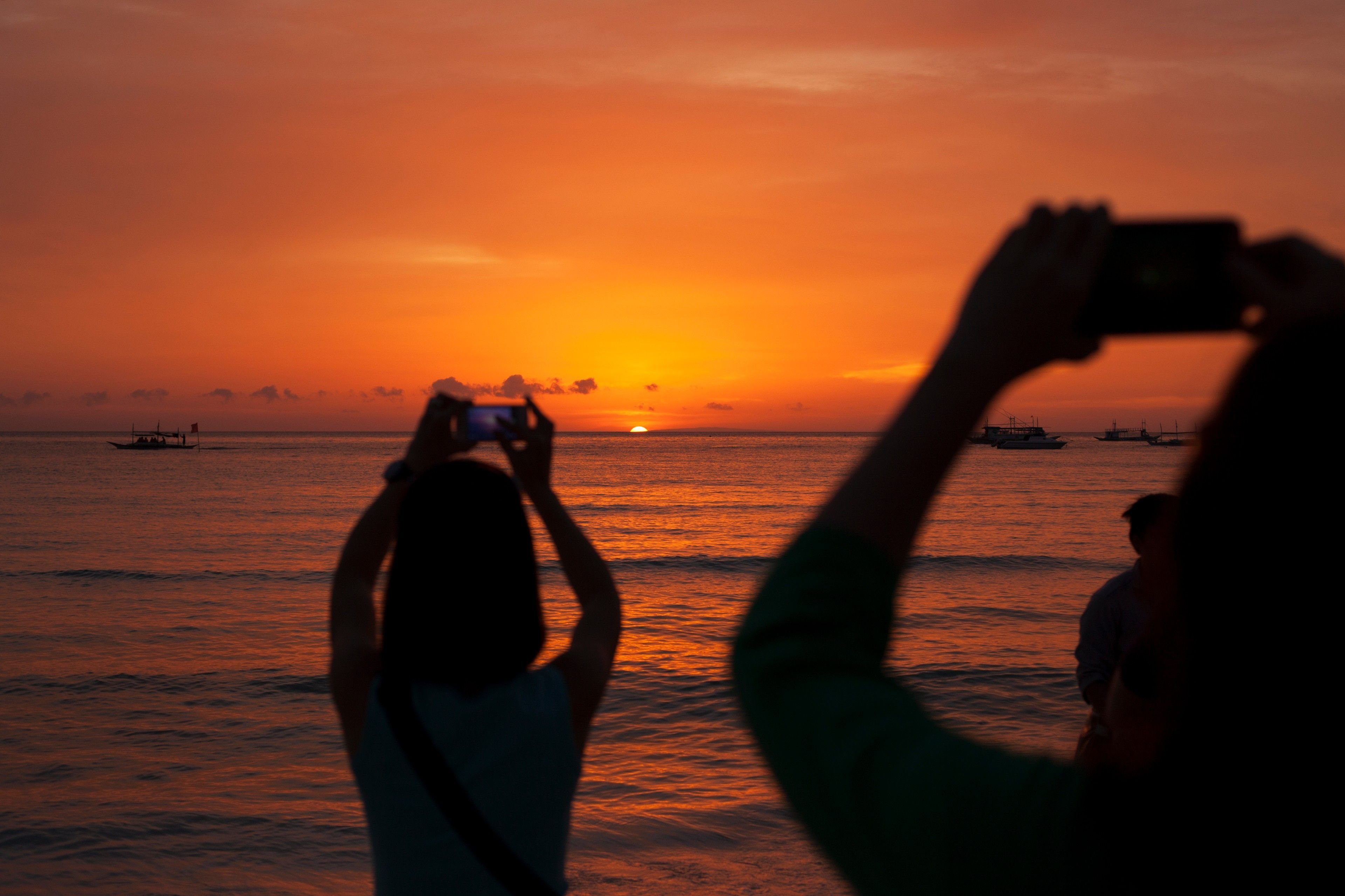 Photo of the Boracay sunset with bystanders taking picture using their phones