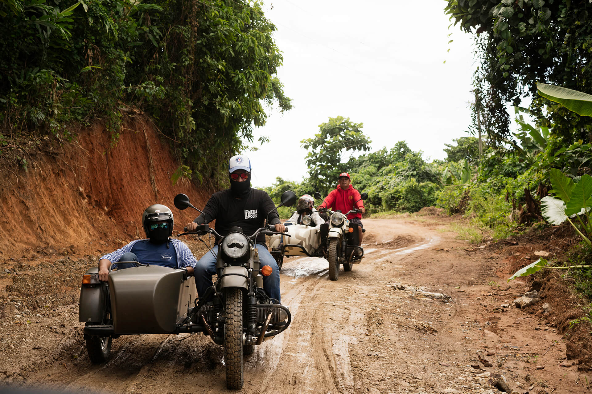 Two Urals with a rider and a passenger each, traversing through muddied roads off the beaten path.