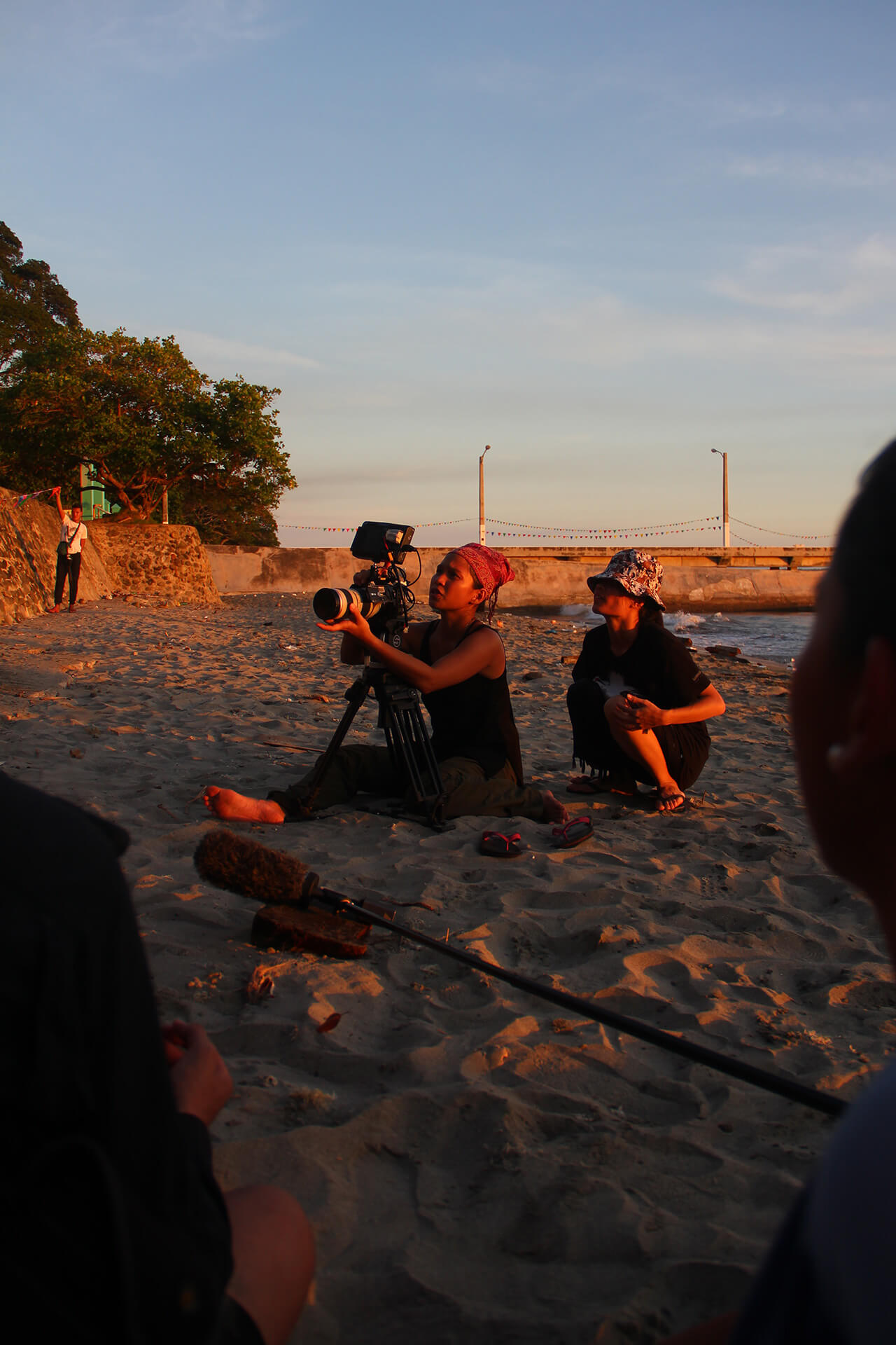 Behind the scenes shot of Ice Idanan shooting by the beach.