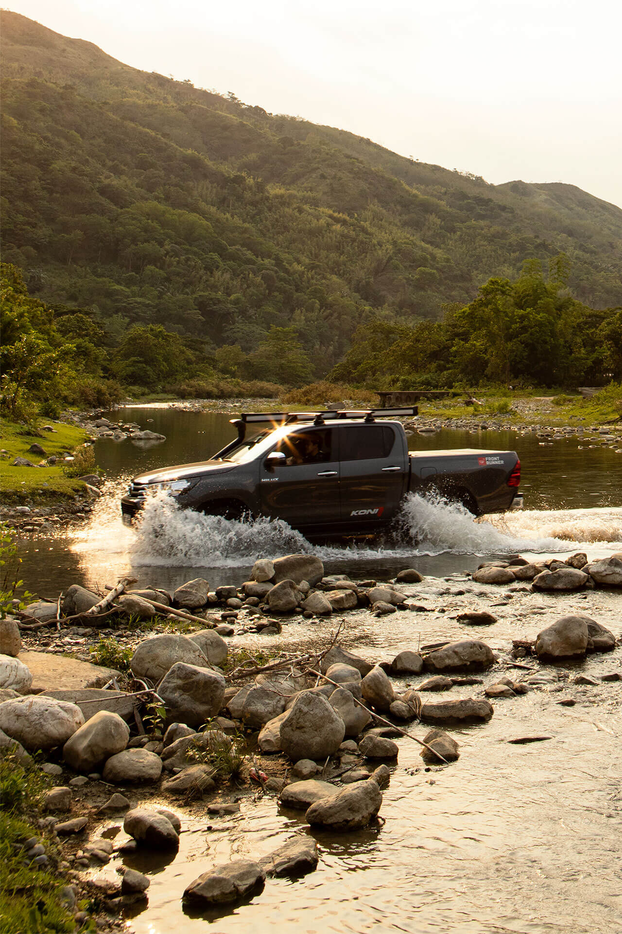 The Toyota Hilux wading through water in the sunset