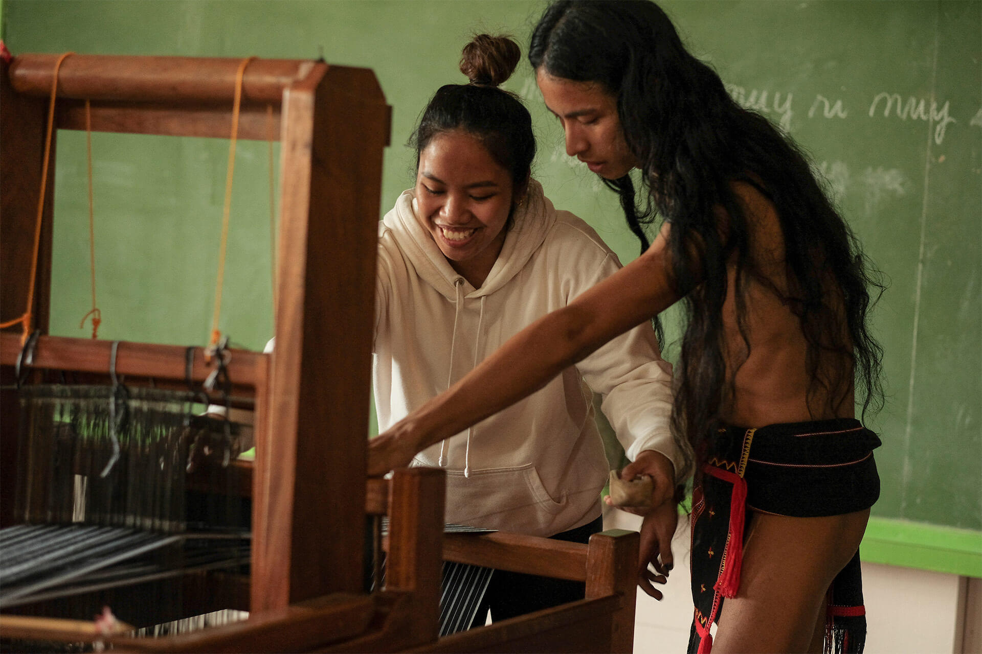 A participant trying out the loom with a native