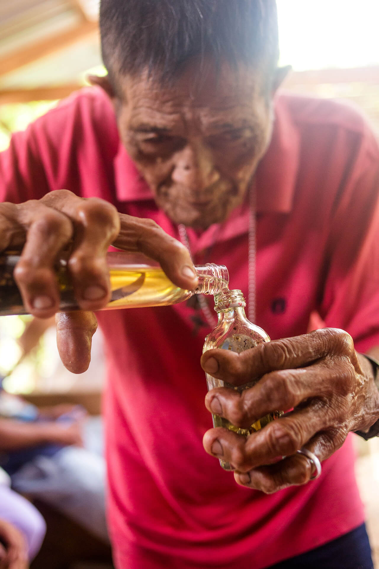 Lolo Bading decants infused coconut oil into a patient's bottle and performs hilot (massage).