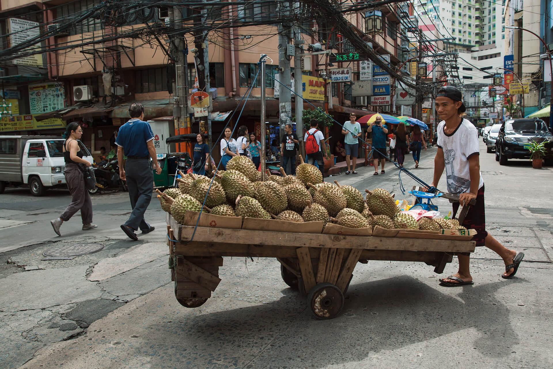 A fruit vendor walking along Ongpin Street
