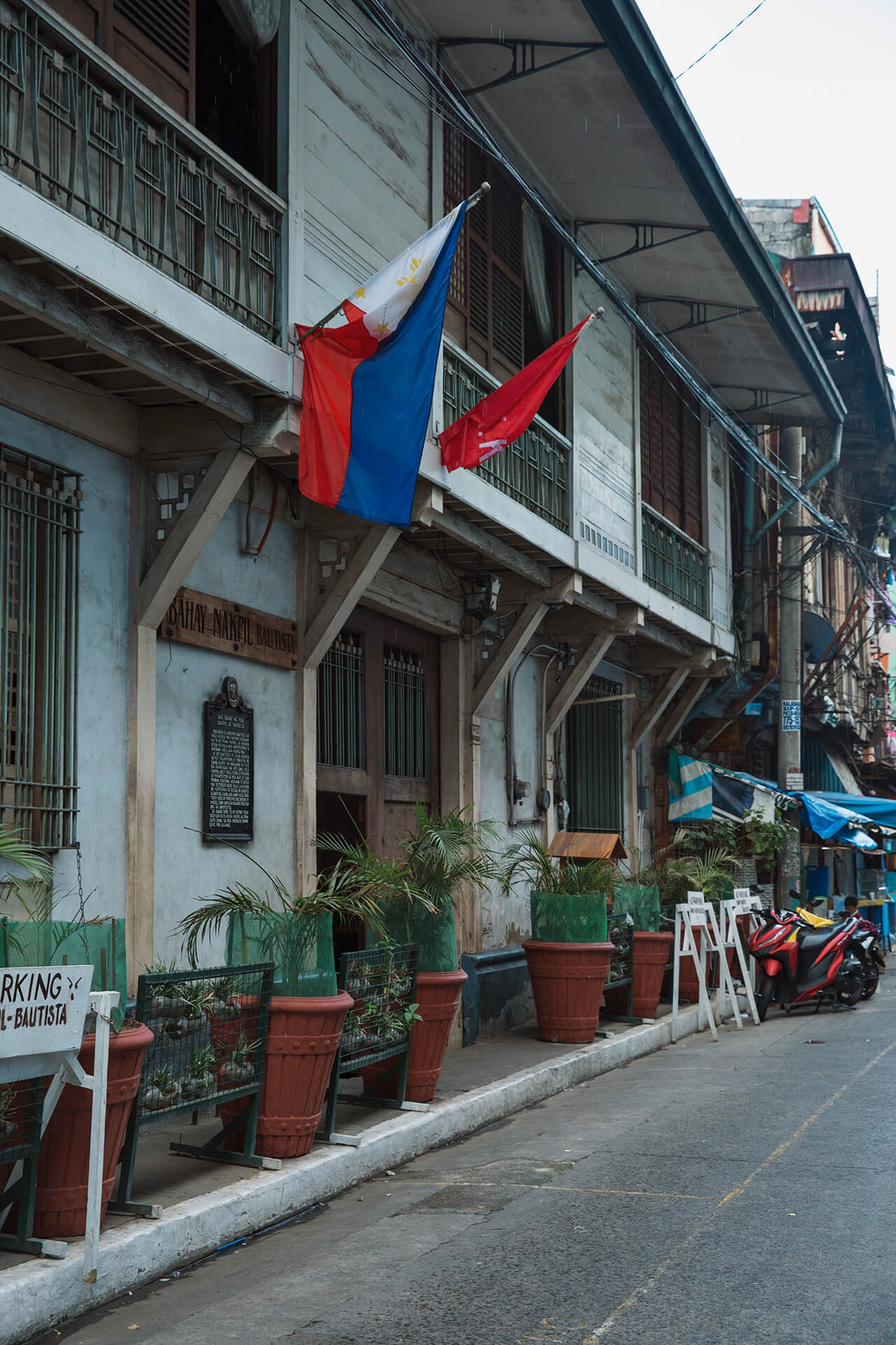 Philippine flags hang from the windows at Bahay Nakpil-Bautista on Barbosa Street