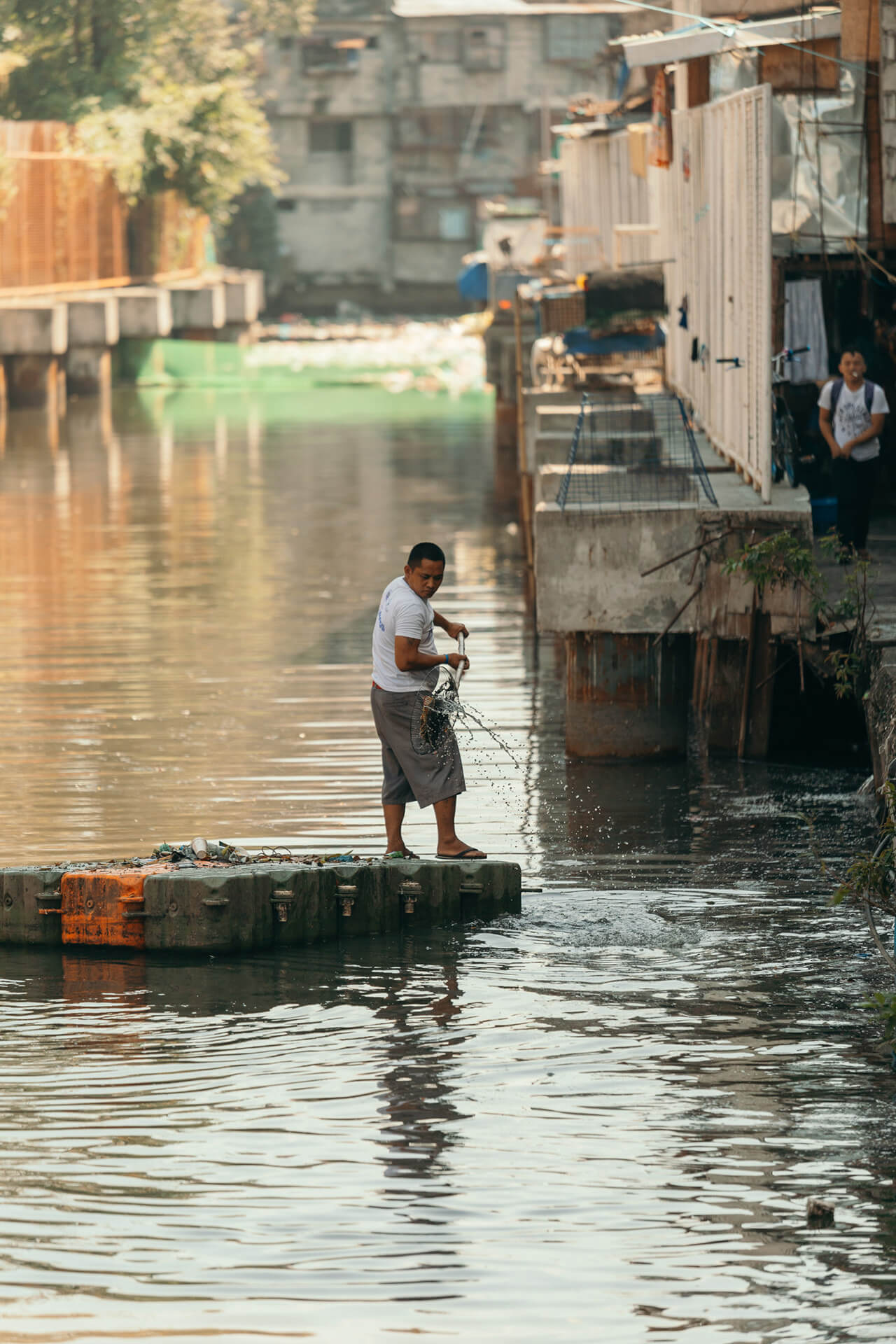 A Pasig River Warrior cleaning Estero de Quiapo while on a makeshift raft