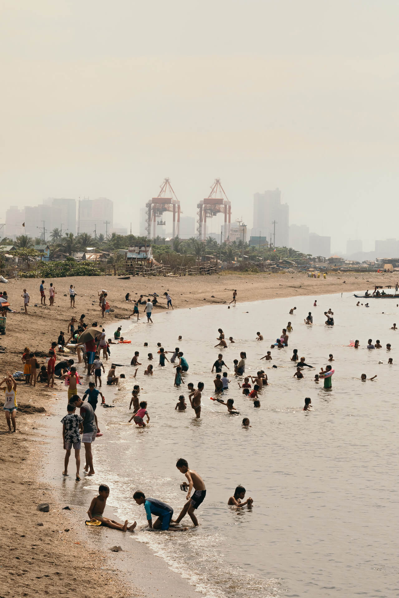 A cleaner Manila Bay with locals relaxing by the shore and shallows.