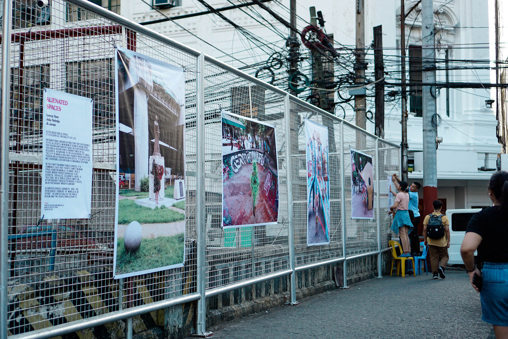 Photos of Alienated Spaces are installed along the fences of Escolta