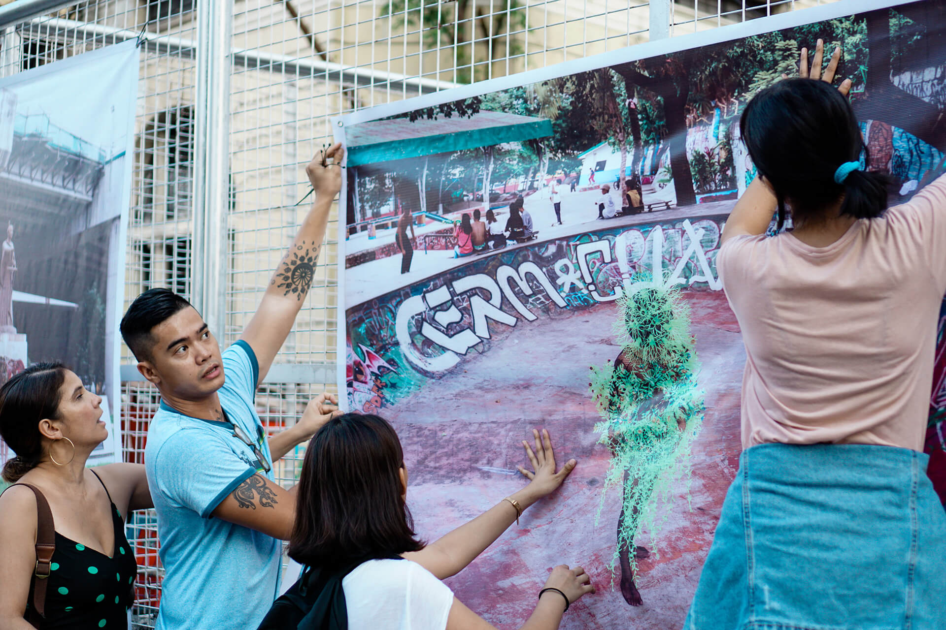 A gallery view of Alienated Spaces is exhibited on a fence along Escolta street.
