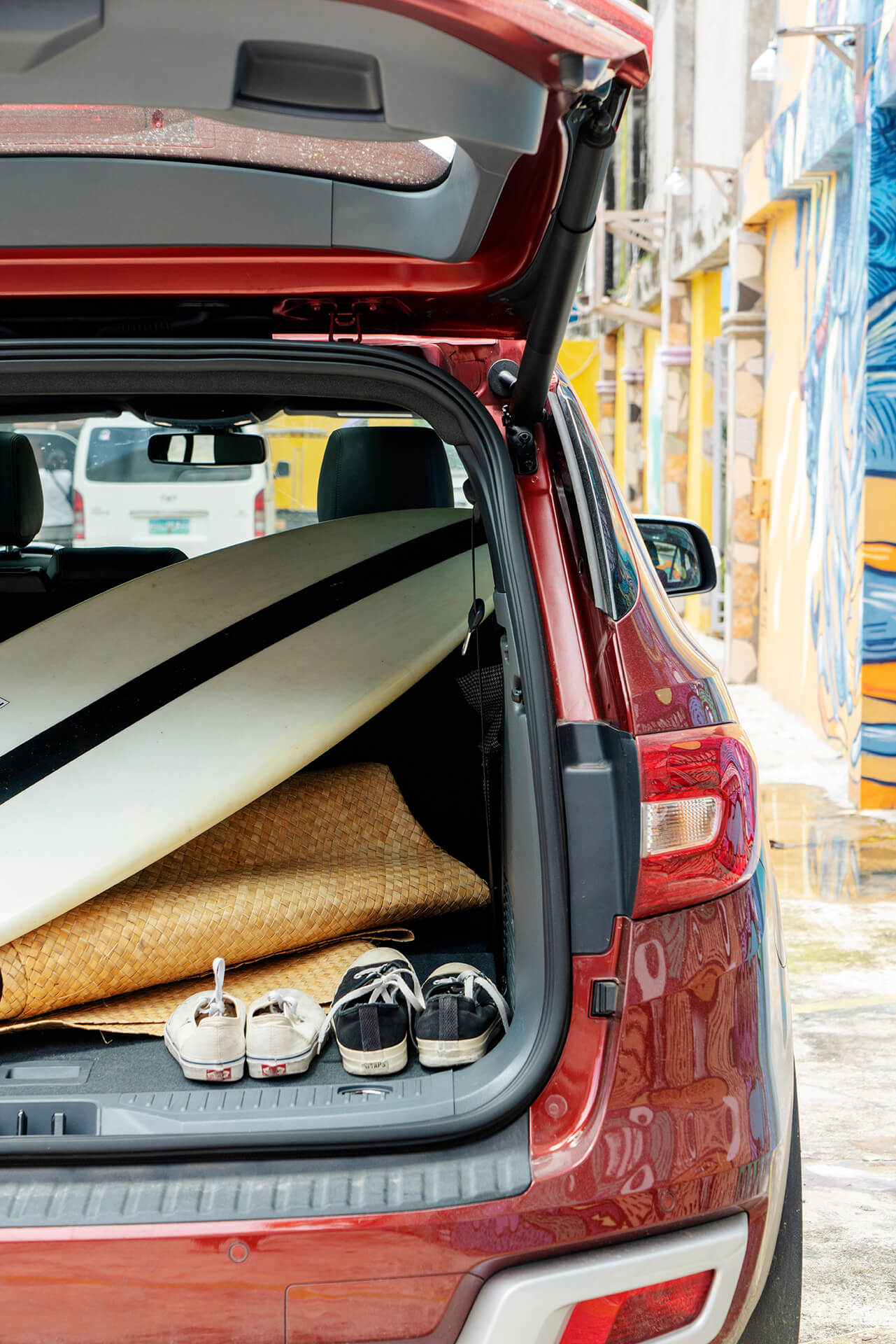 Ford Everest with its trunk open, stuffed with surf boards and other beach paraphernaliah