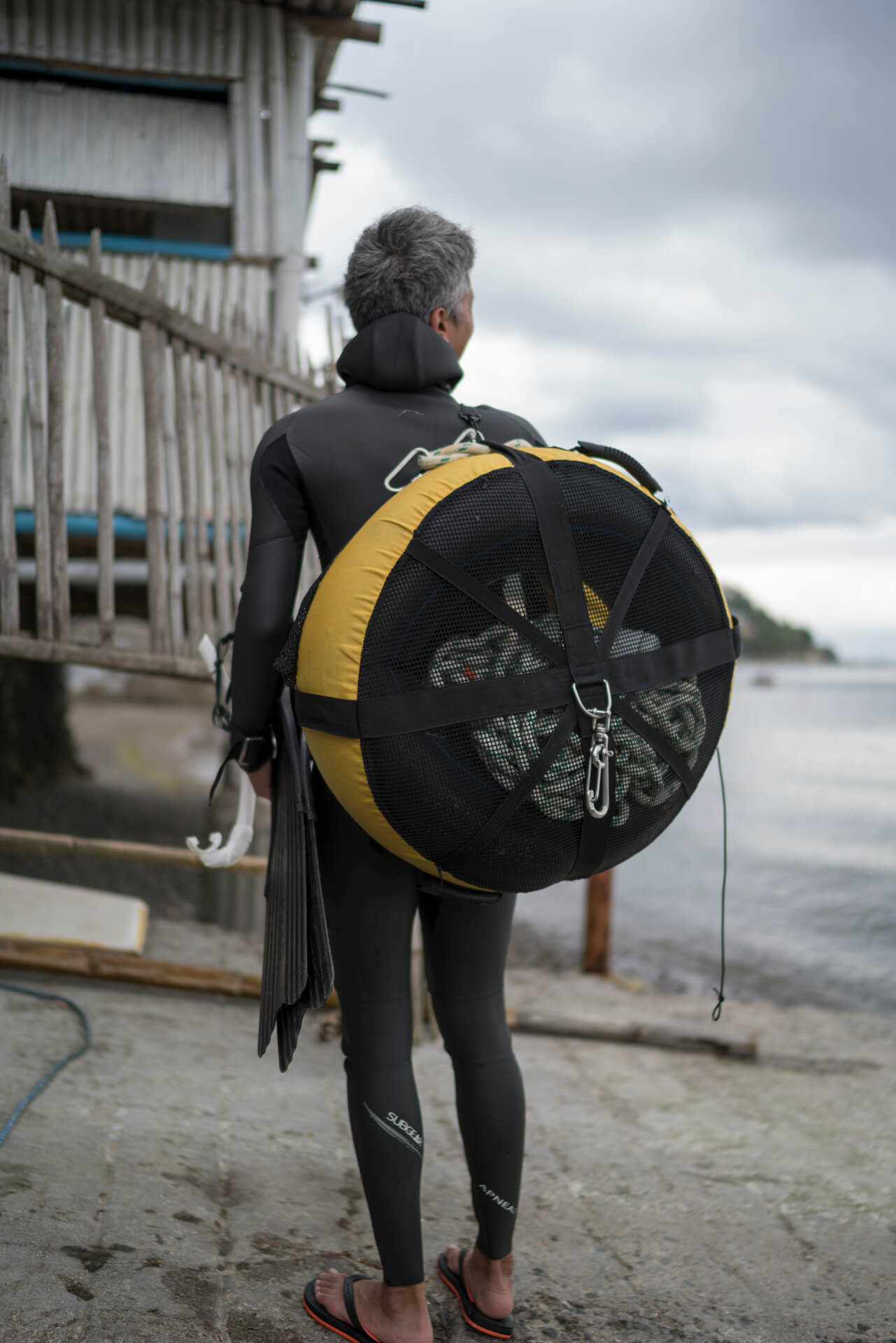 diver carrying gear on shore