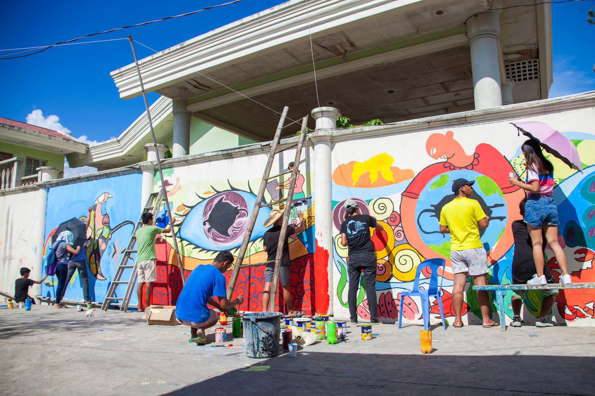 The LAMAVE team painting a mural with the community
