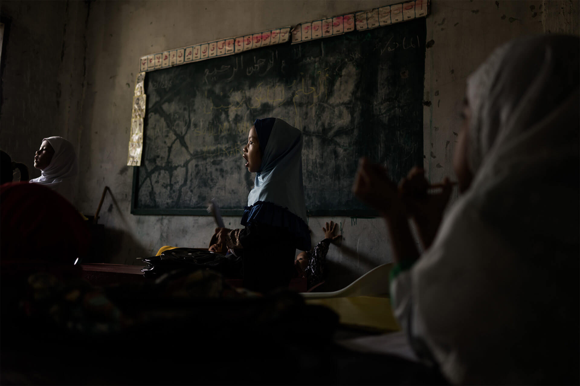 Muslim girl in a classroom with Arabic letter cards in the background