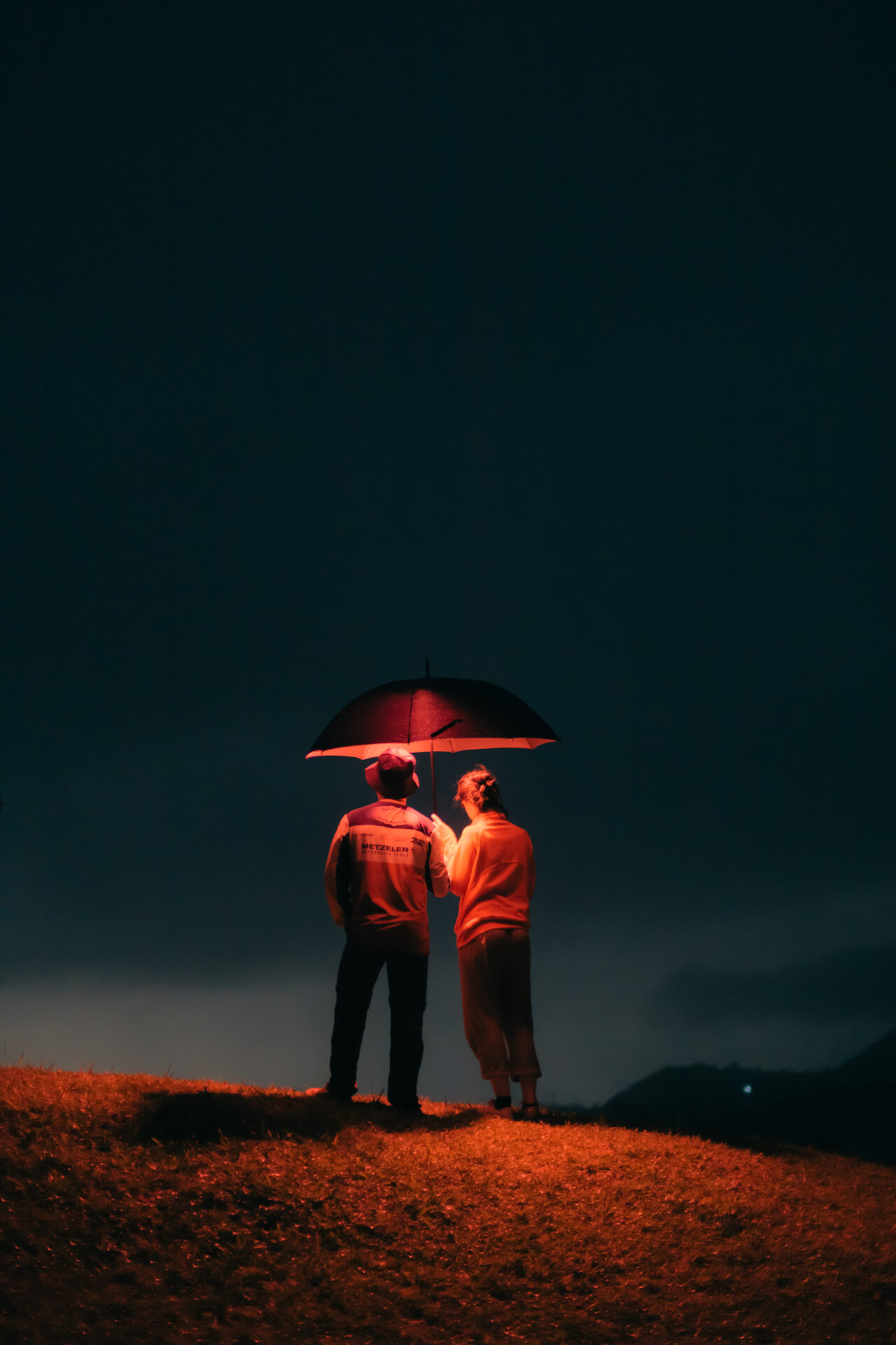 Mike Dee and Denise Gonsalves, under a lit up umbrella, observing a cloudy night sky