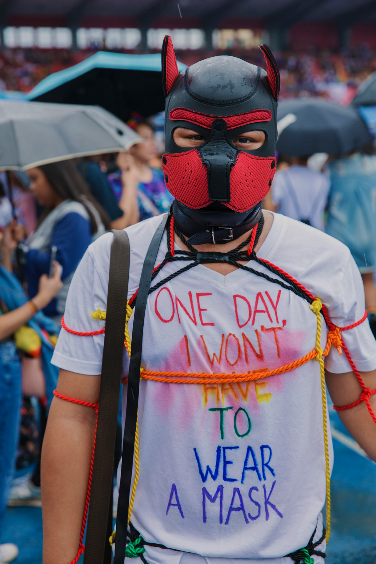 """A person in a mask with ropes tied around them wears a t-shirt saying, """"One day, I won't have to wear a mask."""""""