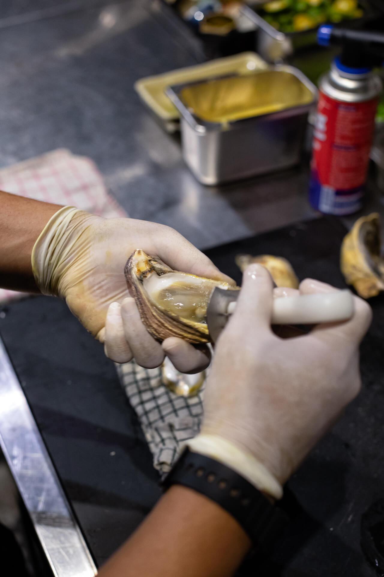 A worker shucking oysters at Wantusawa