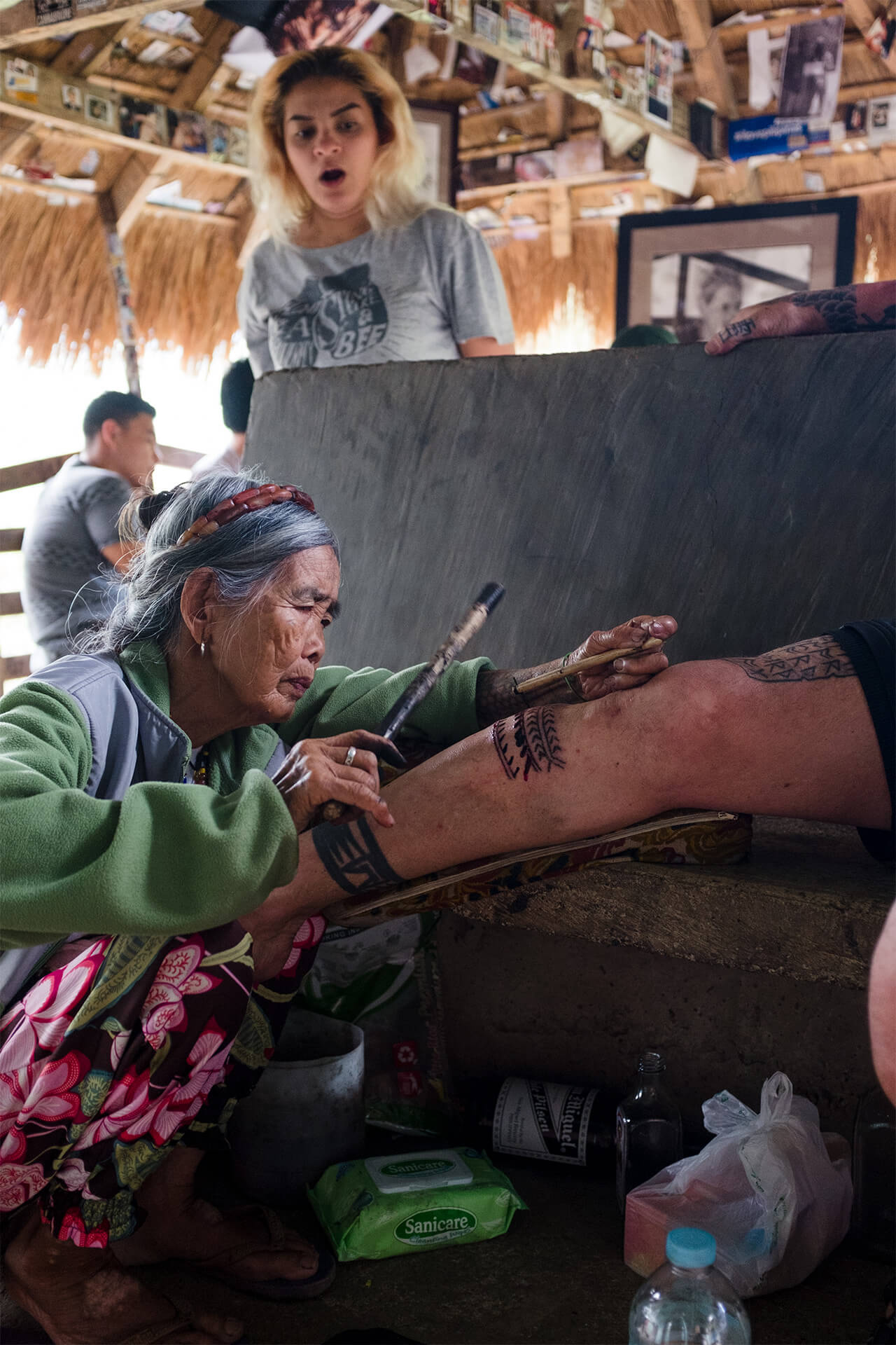 A woman looks with shock at Whang-od tattooing someone's leg