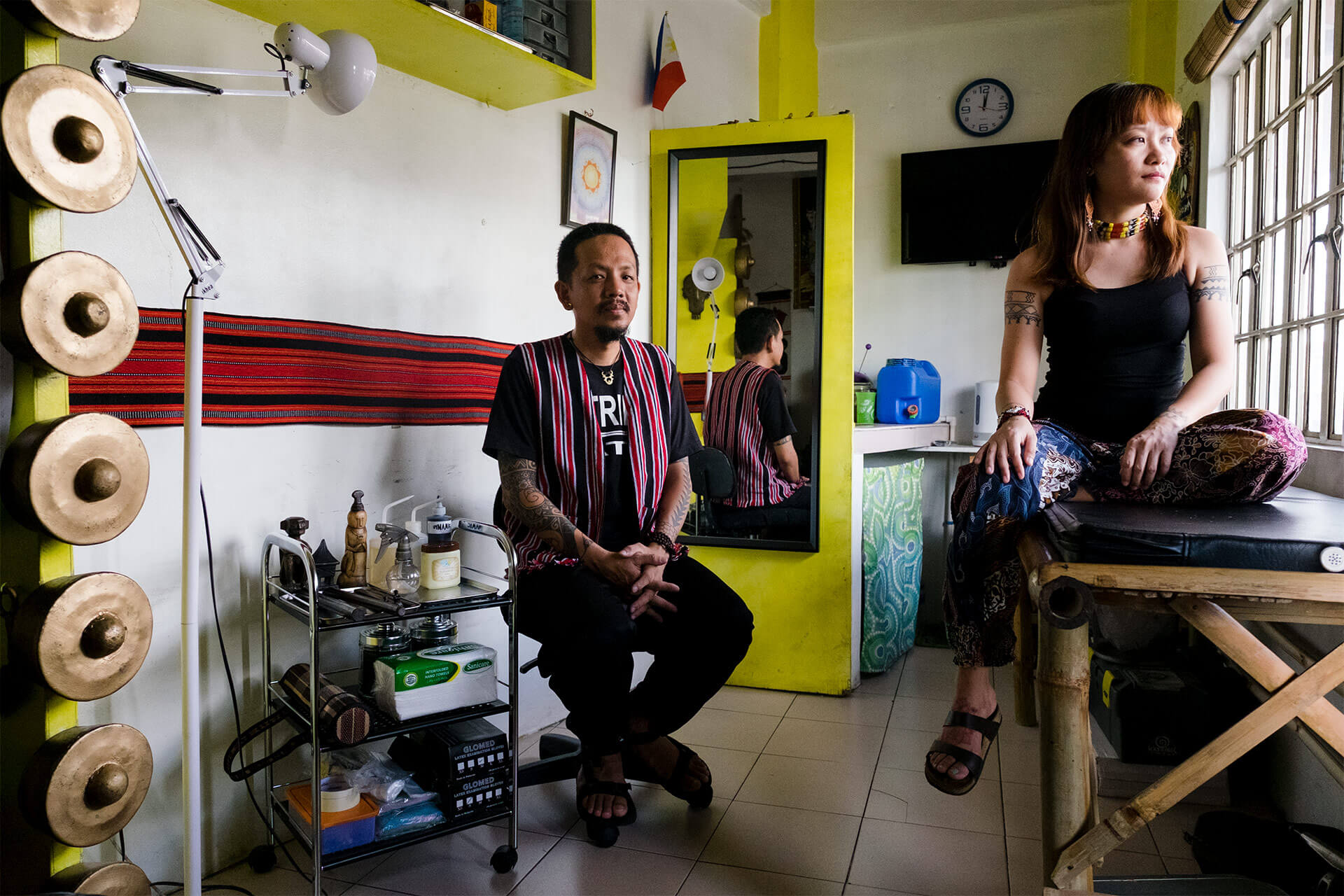 Jean and Jonathan of Katribu in their tattoo parlor, surrounded by pieces from their travels around the Philippines.