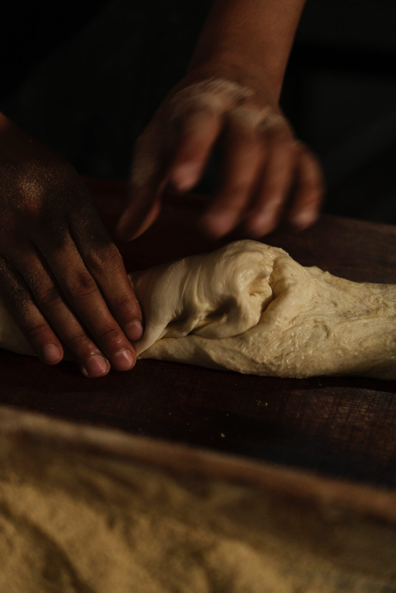 A baker kneads and shapes the dough to prepare it for cutting