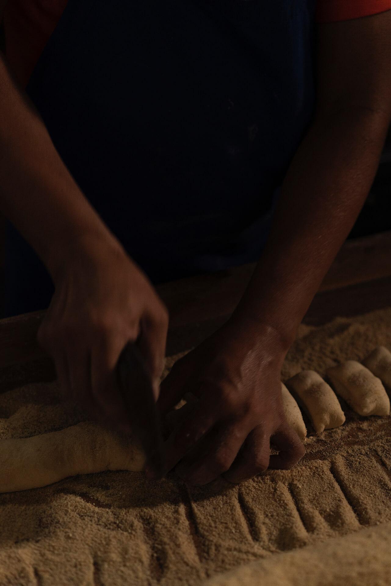 A bakery worker cuts the dough into pan de sal