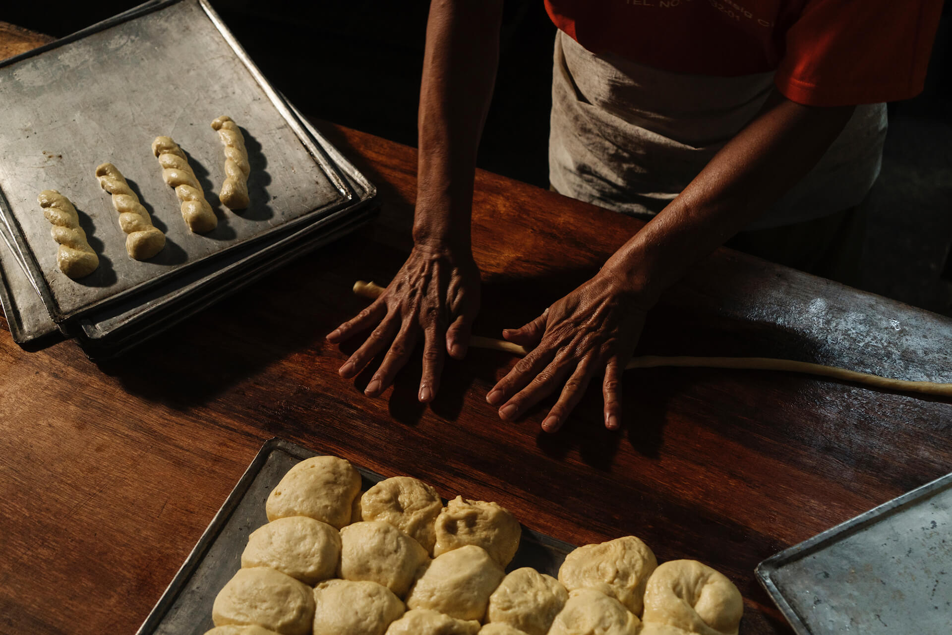 A baker at Panaderia Dimas-Alang shapes the dough for other baked goods