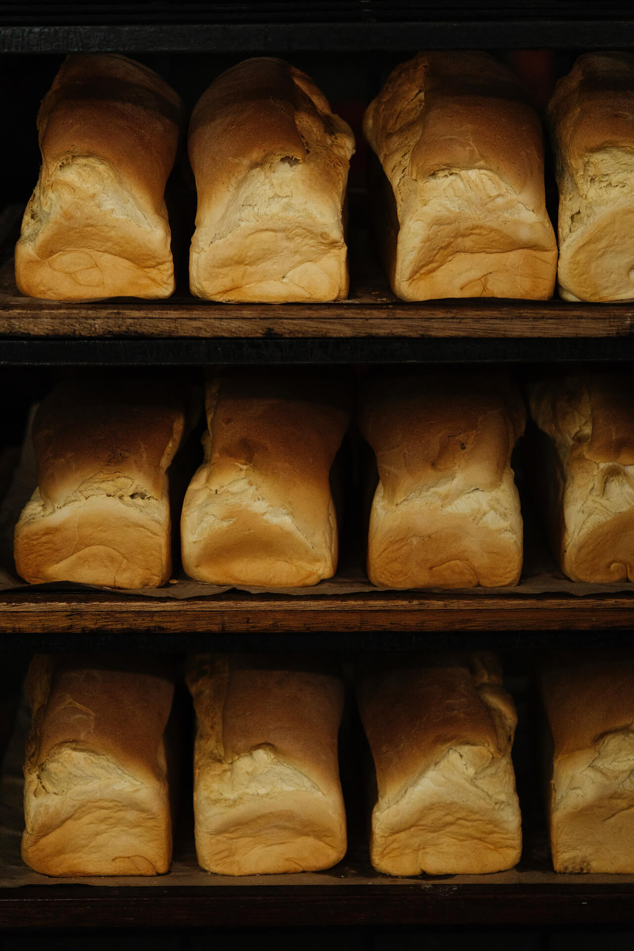 Three shelves of freshly baked loaves of bread