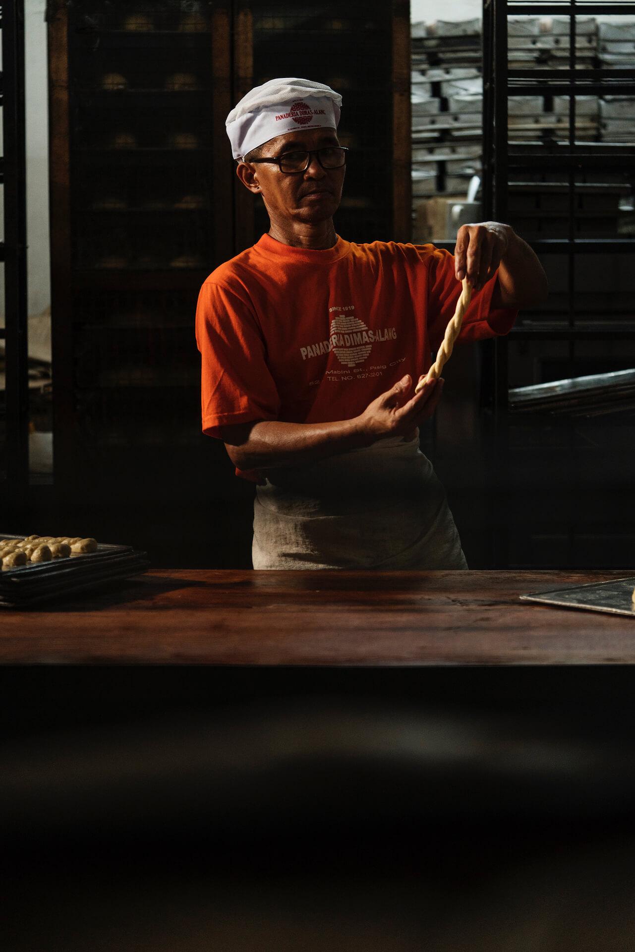 Dominador Caguioa, head baker of Panaderia Dimas-Alang, working with dough