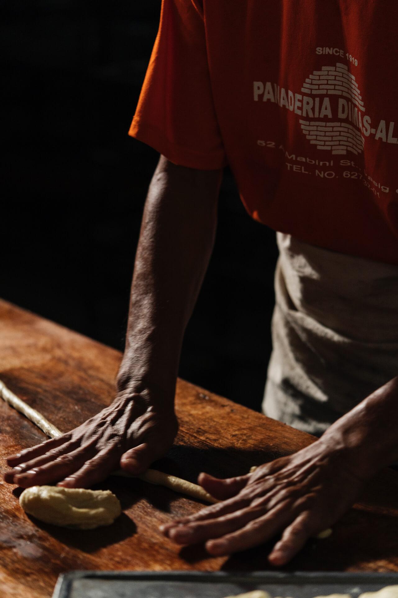 A baker at Panaderia Dimas-Alang shaping dough