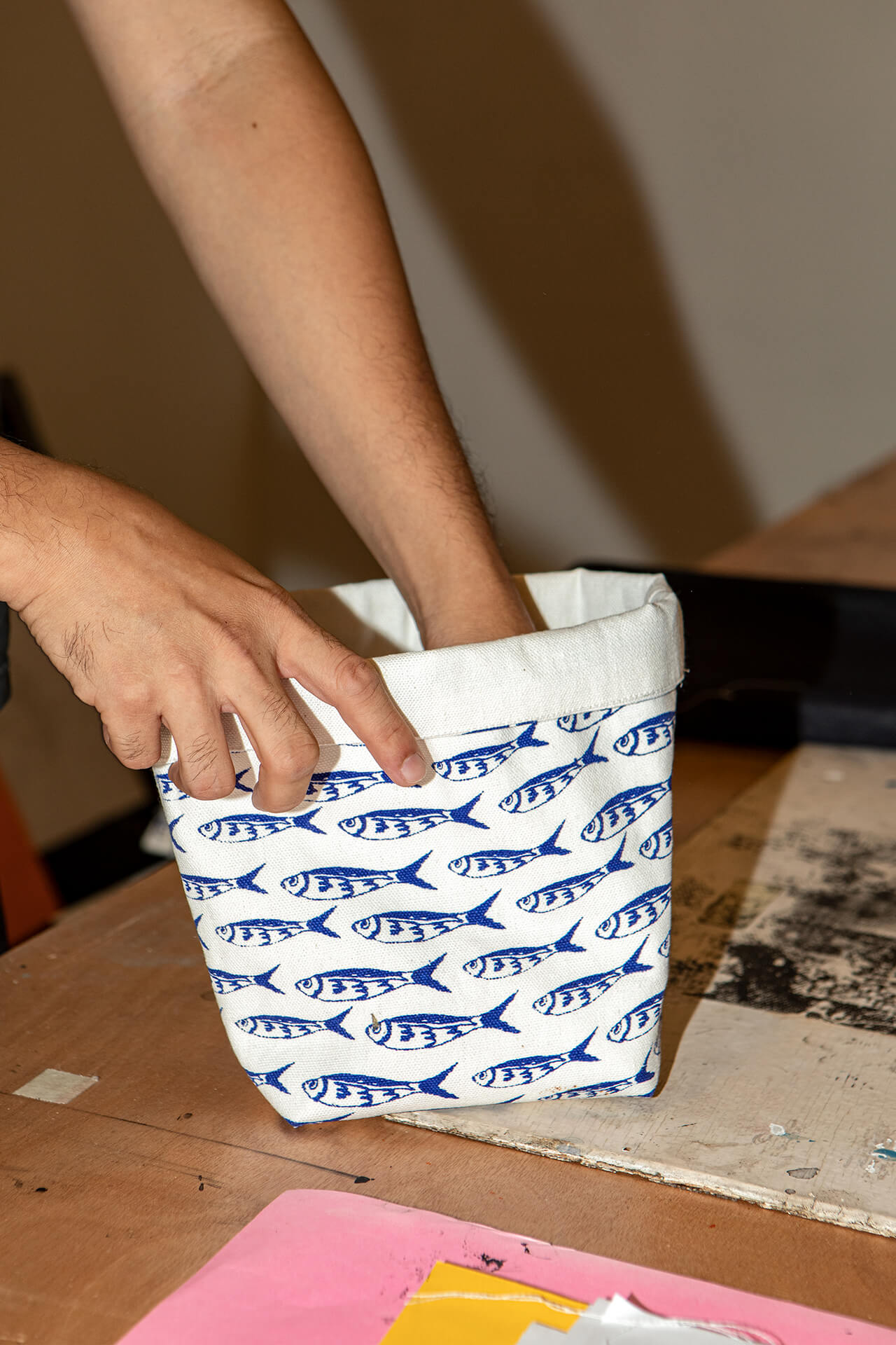 A canvas pouch with a screen printed fish design