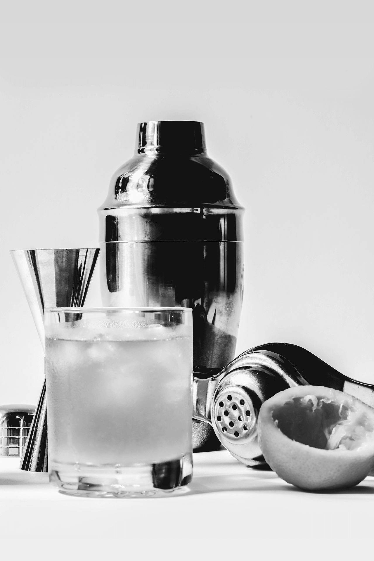 Mixology kit including a jigger, shaker, and a cocktail strainer.